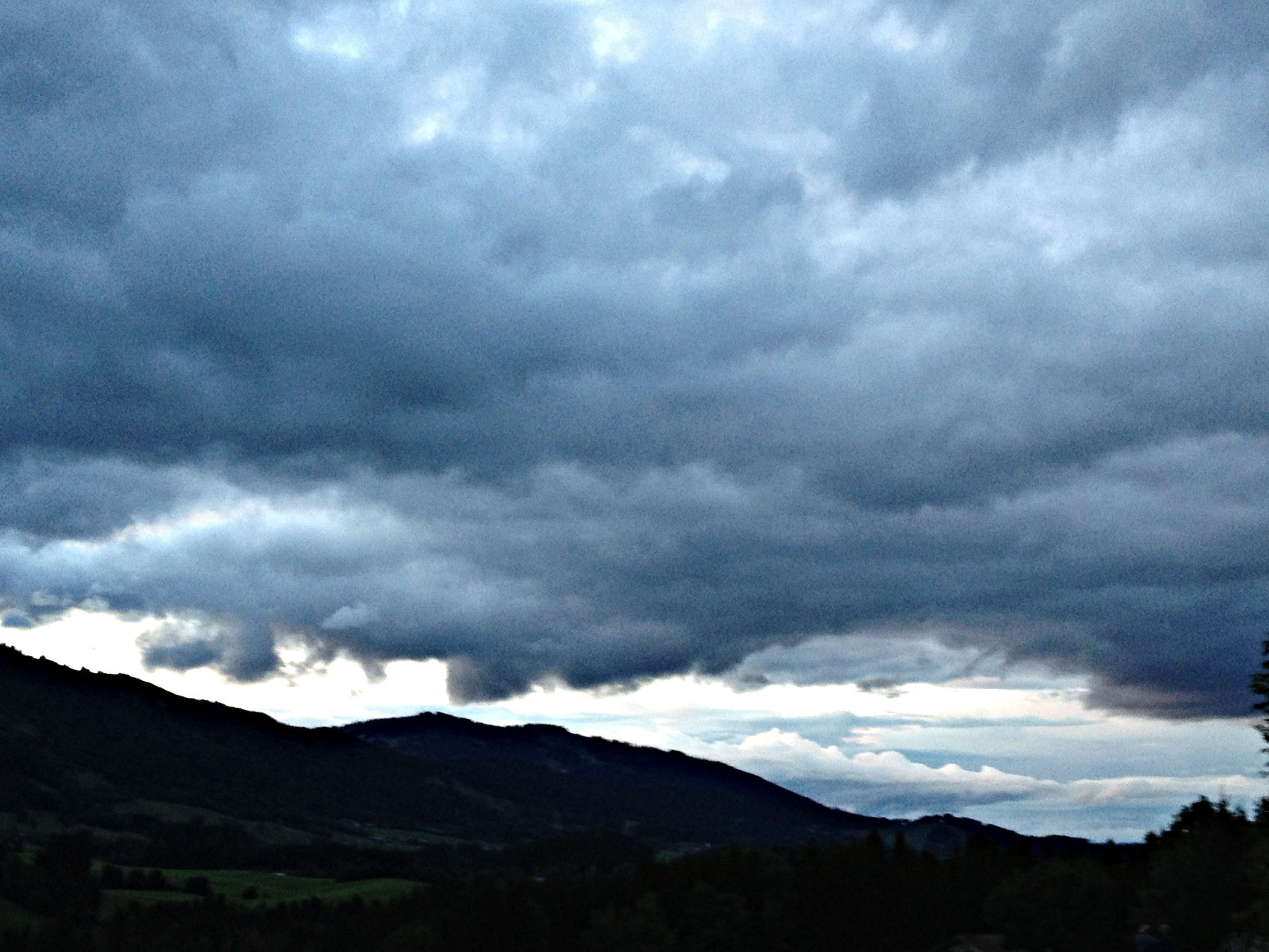 sky, mountain, cloud - sky, cloudy, scenics, tranquil scene, tranquility, beauty in nature, mountain range, weather, silhouette, nature, overcast, cloud, landscape, low angle view, cloudscape, storm cloud, dusk, idyllic