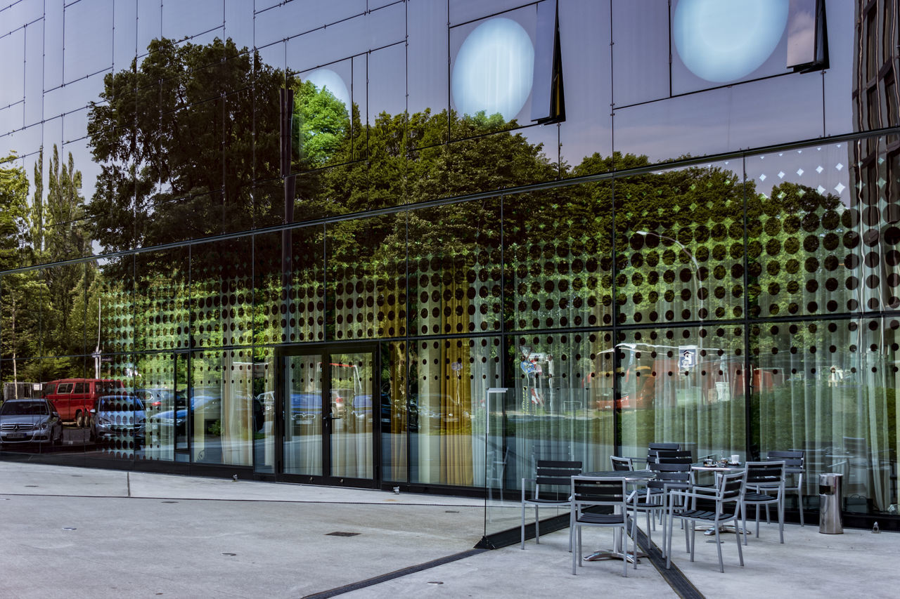 ArcotelOnyx Architecture Building Exterior Built Structure Chairs And Tables City Day Facades Glass Fronted Building Glass Reflection Hamburg Reeperbahn Modern Architecture No People Outdoors Reflections Seats Tourist Attraction  Tree