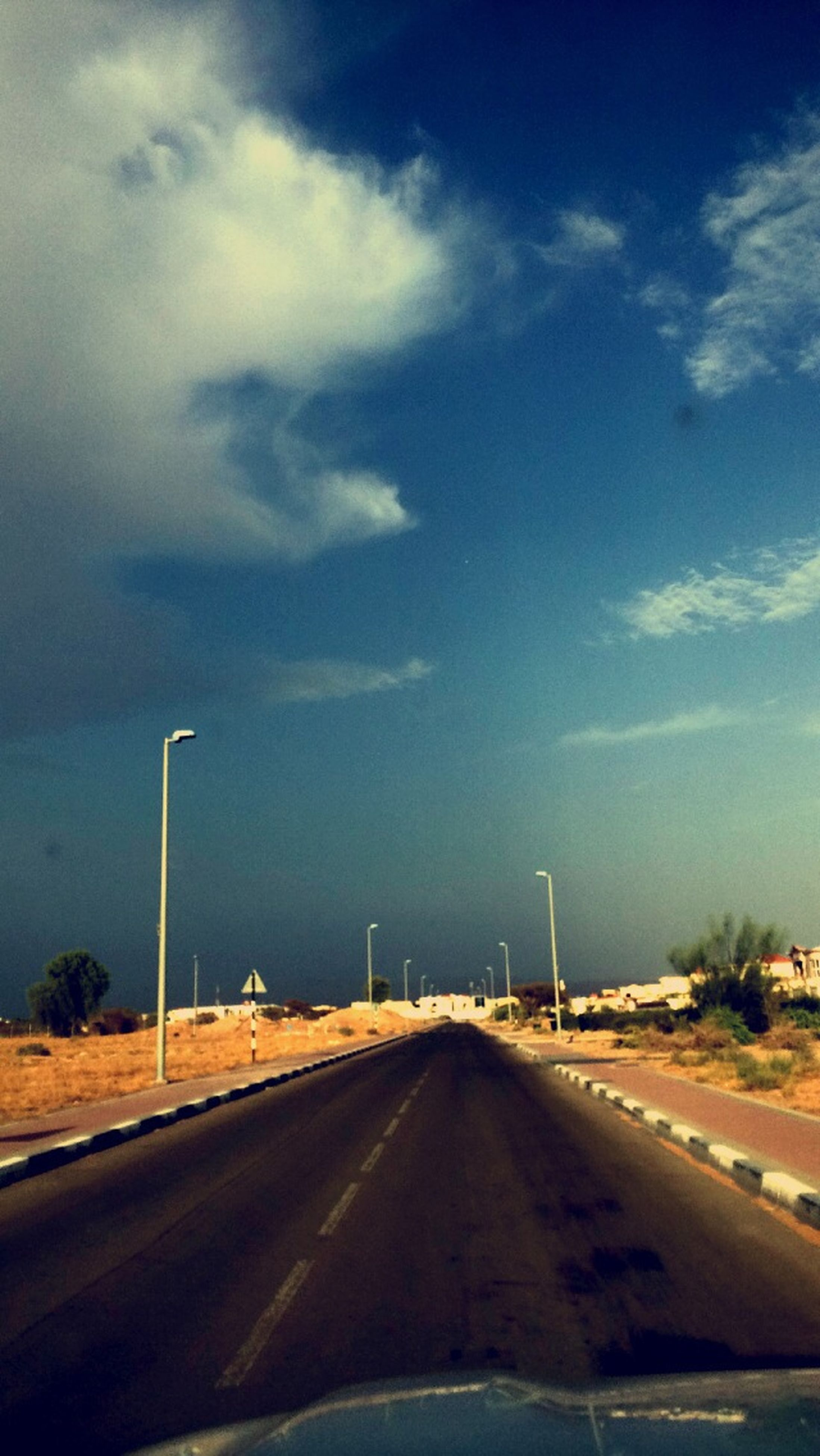 the way forward, road, sky, transportation, diminishing perspective, road marking, vanishing point, cloud - sky, street light, street, empty, asphalt, empty road, cloud, country road, cloudy, long, blue, outdoors, nature