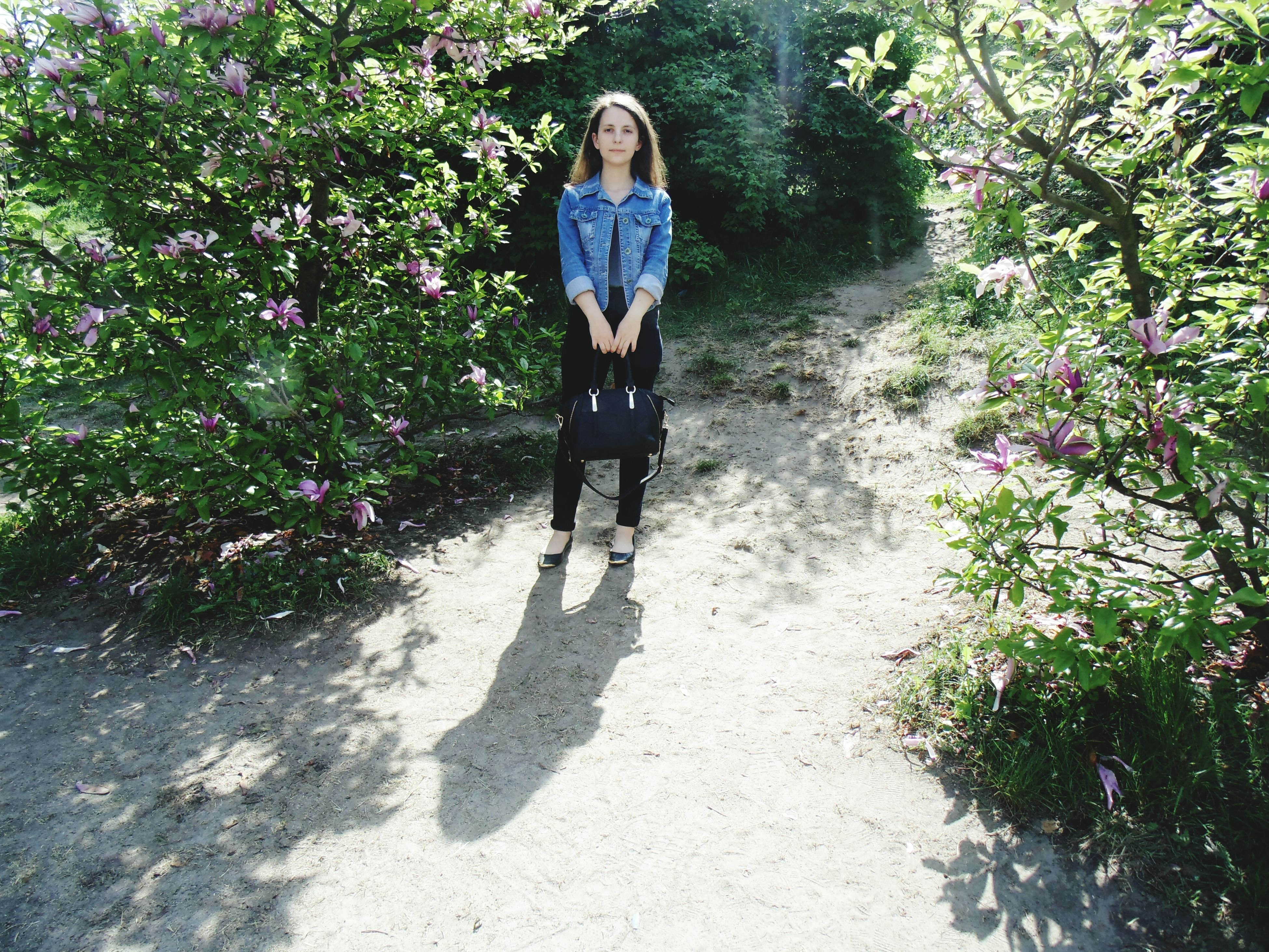 real people, front view, full length, one person, day, plant, lifestyles, young women, nature, leisure activity, outdoors, young adult, tree, casual clothing, sunlight, growth, standing, shadow, looking at camera, beautiful woman, flower, people