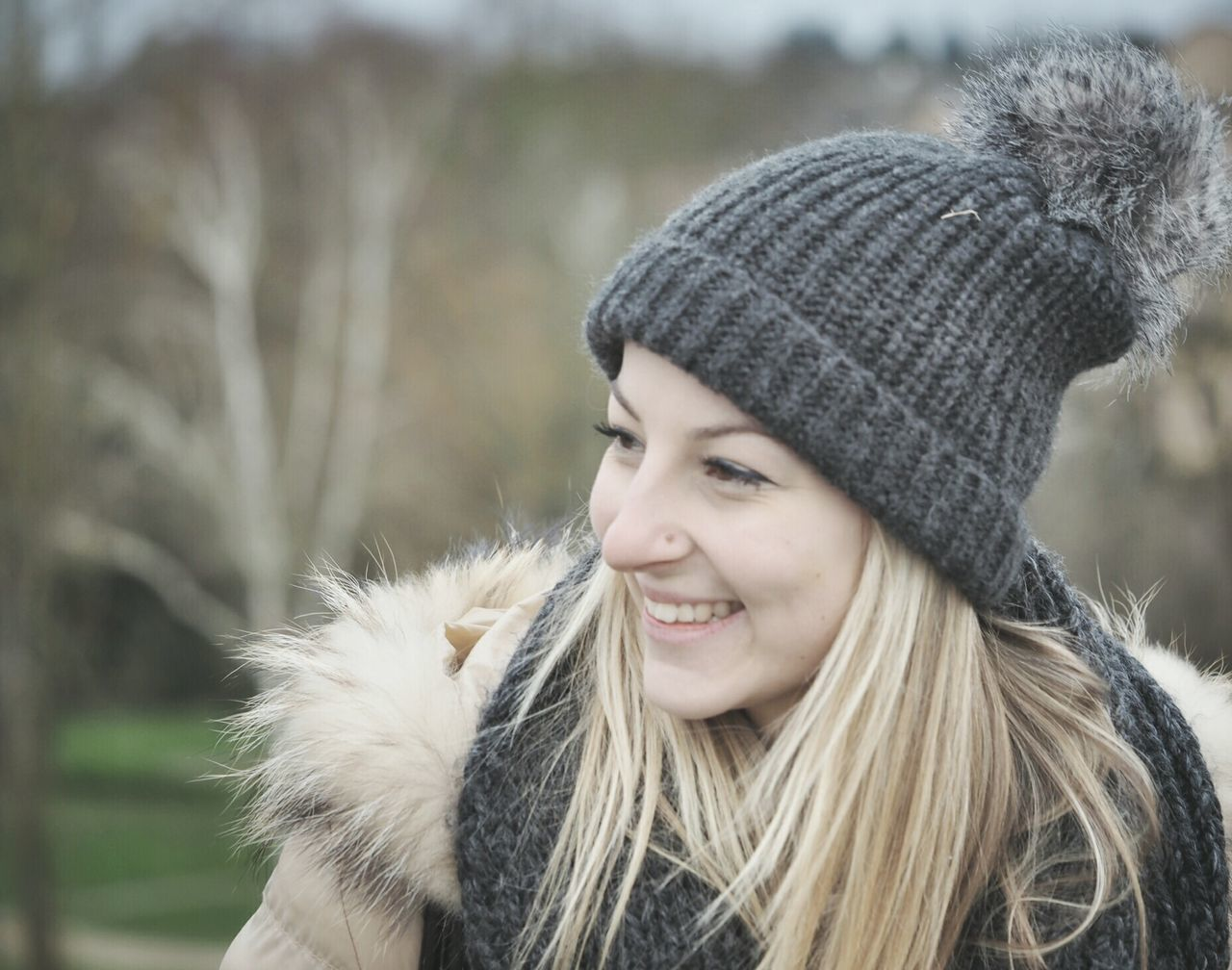 knit hat, warm clothing, real people, one person, focus on foreground, outdoors, day, winter, headshot, young women, leisure activity, young adult, smiling, front view, long hair, close-up, lifestyles, cold temperature, happiness, nature, beautiful woman, blond hair, people