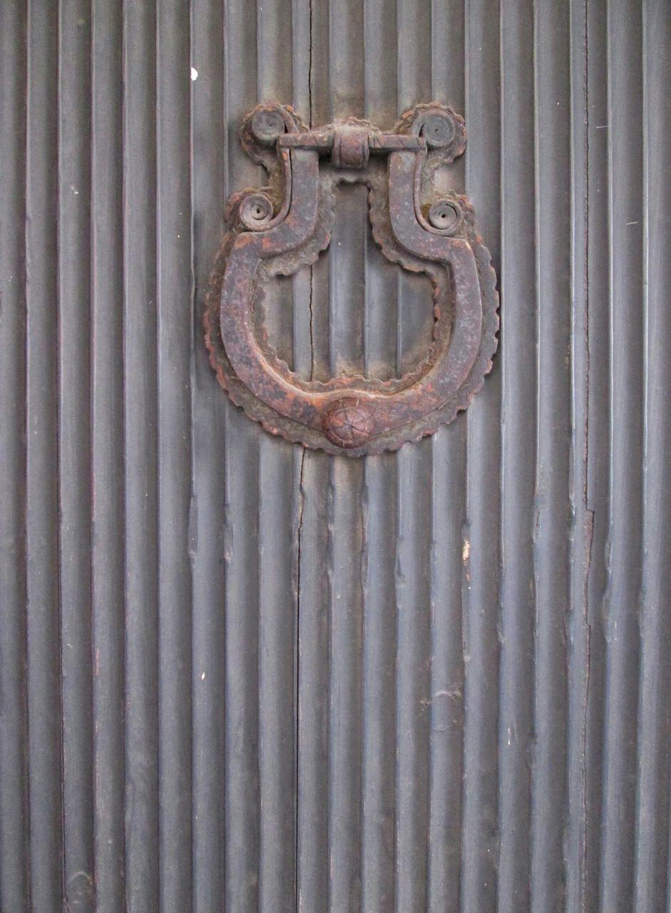 Old Rusty Doorknob On Wooden Door