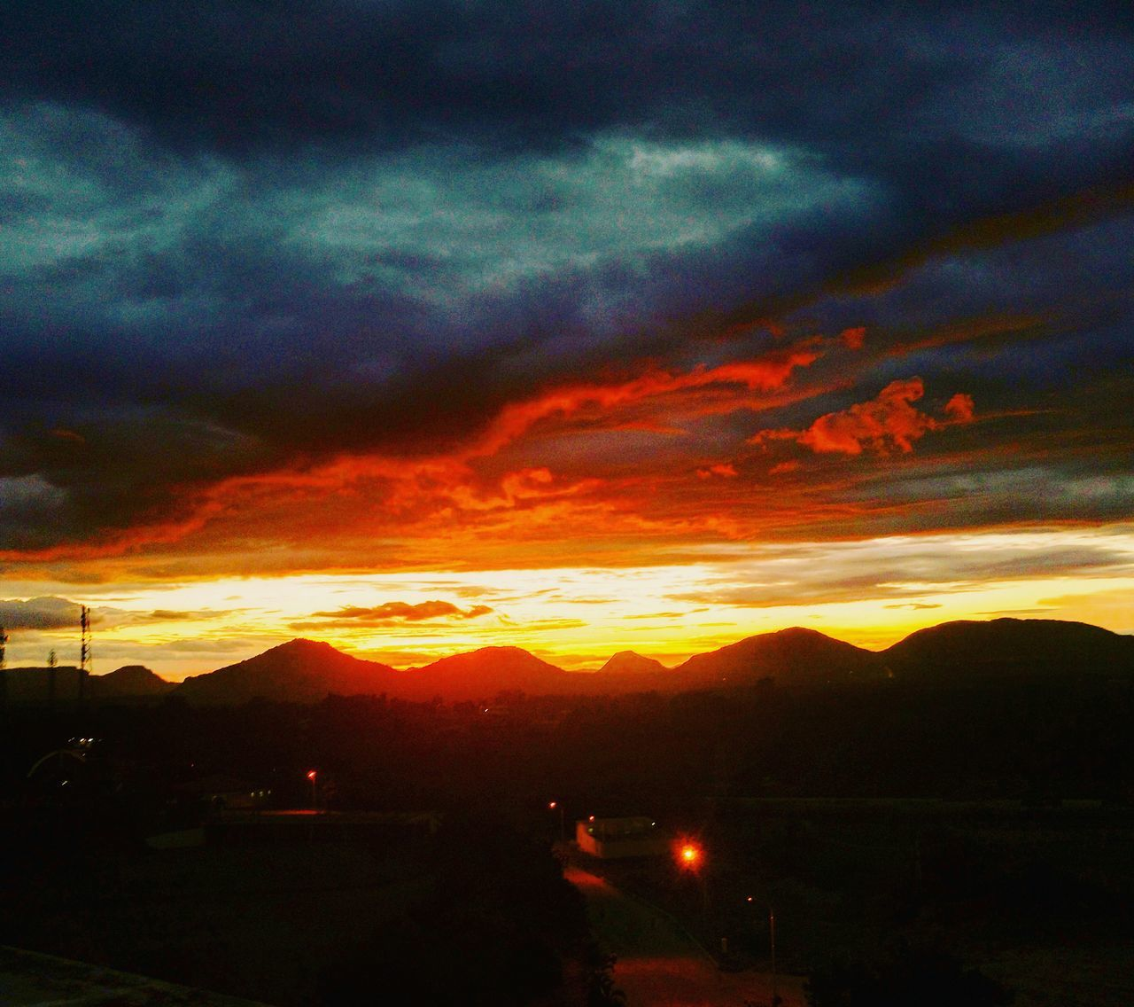 sunset, cloud - sky, sky, dramatic sky, orange color, nature, beauty in nature, scenics, silhouette, no people, tranquility, tranquil scene, outdoors, storm cloud, mountain, landscape, city
