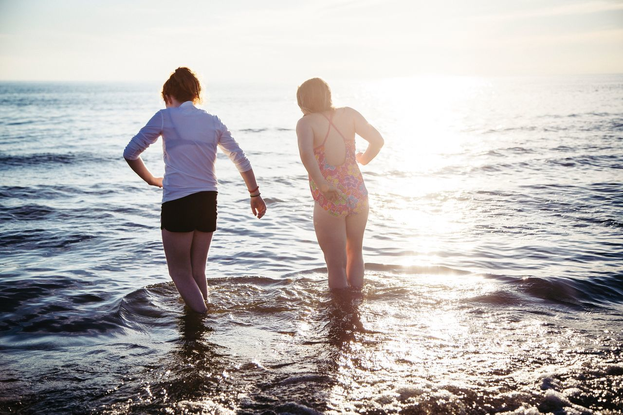 sea, two people, water, real people, horizon over water, leisure activity, nature, togetherness, rear view, sunset, lifestyles, beauty in nature, scenics, sky, standing, beach, full length, sunlight, love, vacations, outdoors, ankle deep in water, young women, women, bonding, young adult, day, friendship