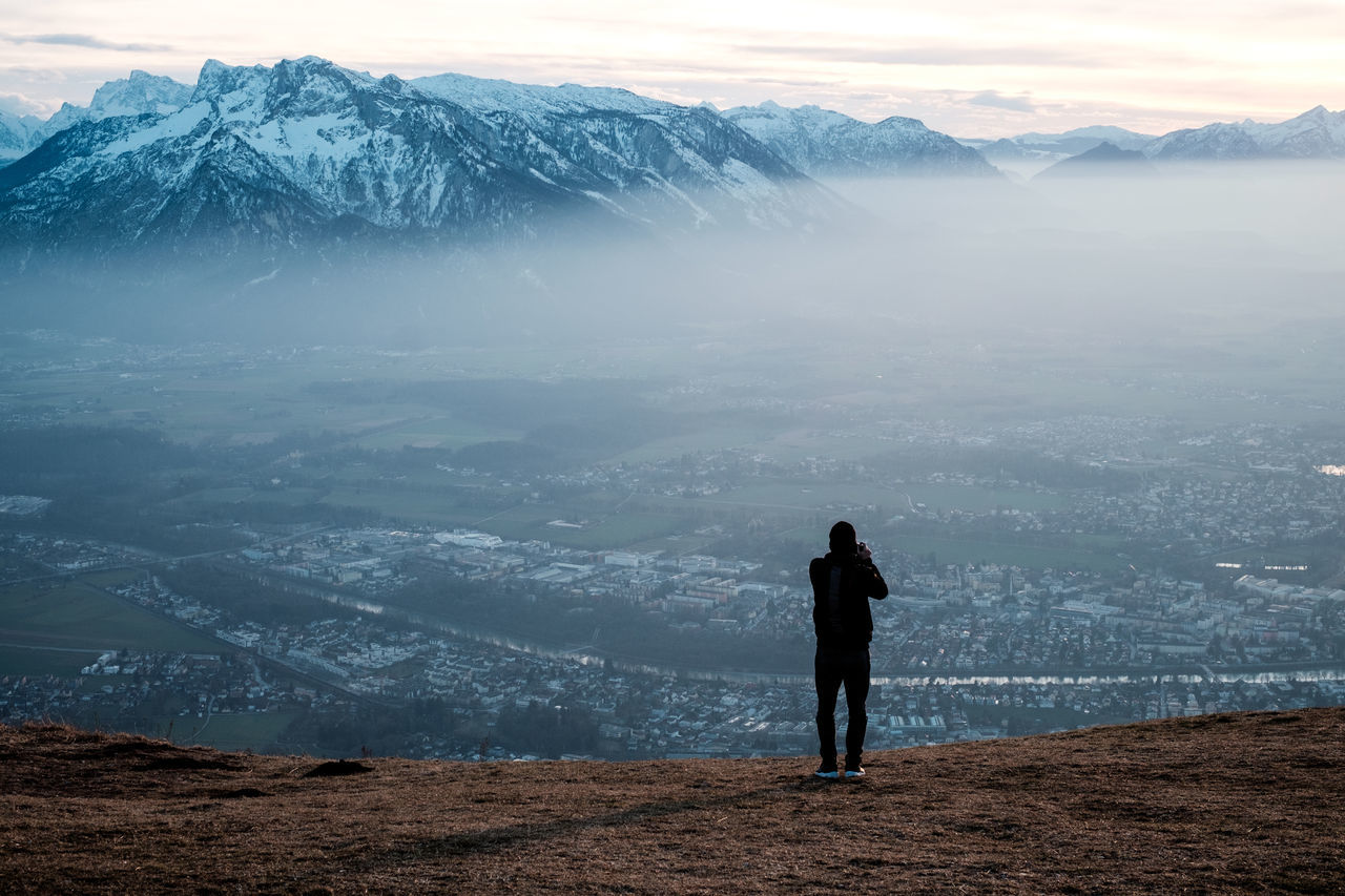 Adult Adventure Beauty In Nature Cloud - Sky Cold Temperature Day Fog Freedom Full Length Landscape Man Mountain Mountain Range Nature Outdoors Photographer Real People Rear View Snow Snowcapped Mountain Standing Travel Destinations Vacations View Winter