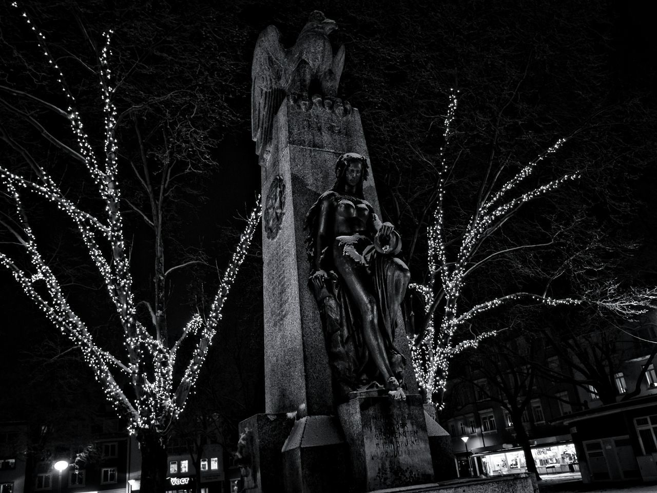 Low Angle View Of Statue Amidst Illuminated Trees At Night