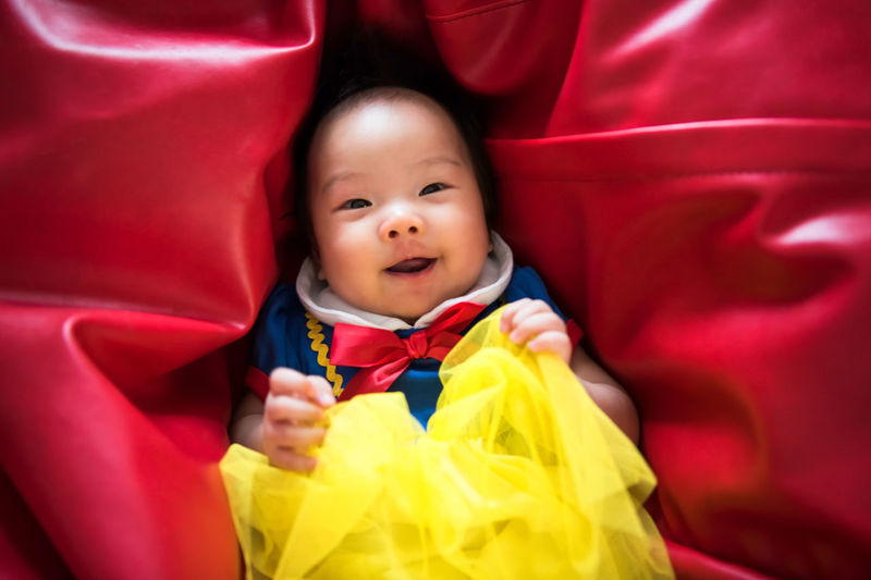 Portrait of happy cute Asian baby, 3 months old with fantasy outfit costume, relax and lie on vibrant red bean bag. Adorable beautiful white girl look at camera. Red Adorable Babyhood Bean Bag Childhood Close-up Costume Cute Day Girl Indoors  Laugh Lifestyles Looking At Camera Newoneyeem One Person People Portrait Real People Red Smiling Snow White