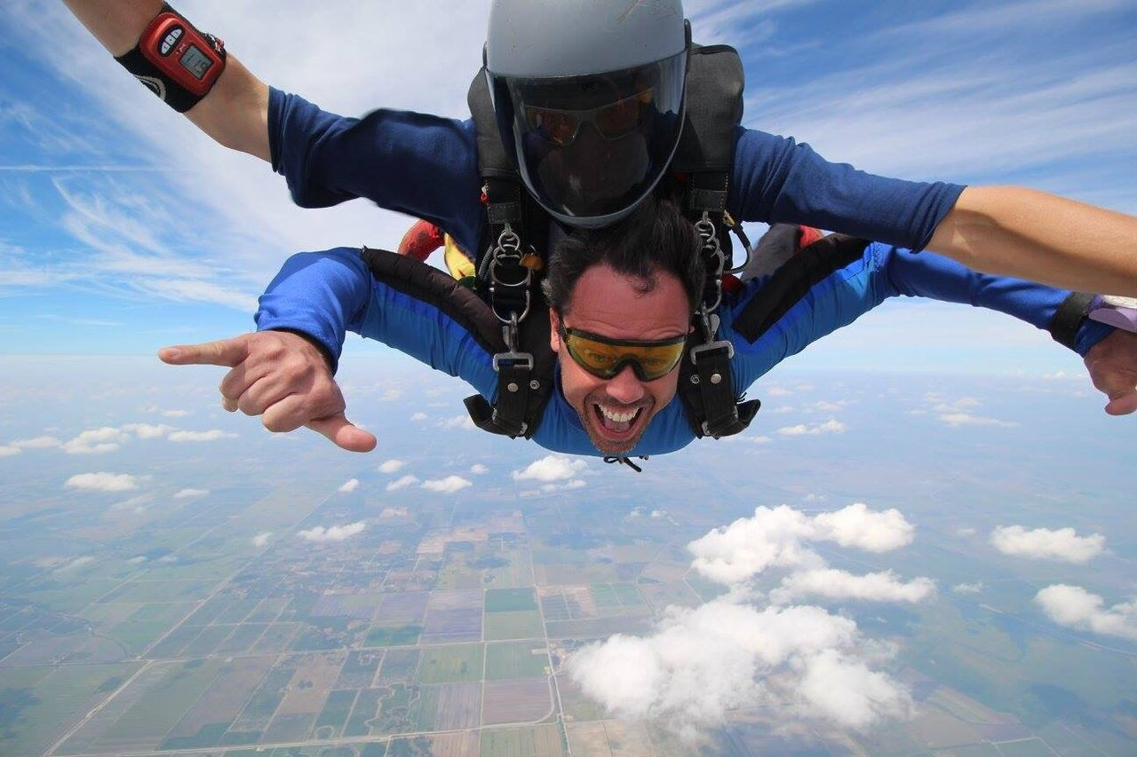 skydiving, adventure, exhilaration, leisure activity, real people, sky, extreme sports, mid-air, parachute, helmet, lifestyles, cloud - sky, day, flying, outdoors, men, motion, airplane, nature, human hand, people