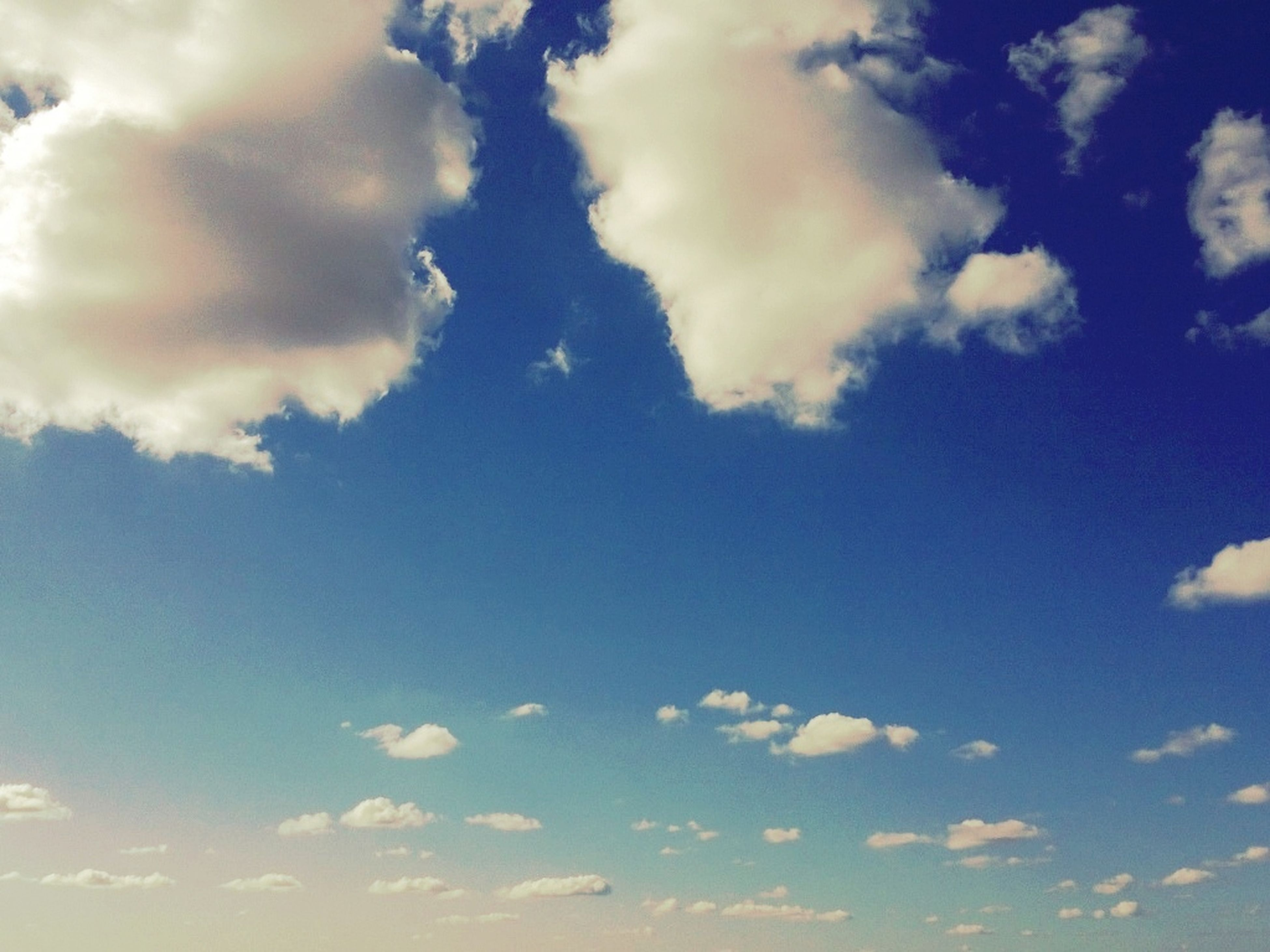 sky, cloud - sky, low angle view, beauty in nature, blue, tranquility, scenics, cloudy, nature, tranquil scene, sky only, cloud, cloudscape, backgrounds, idyllic, outdoors, day, no people, full frame, white color