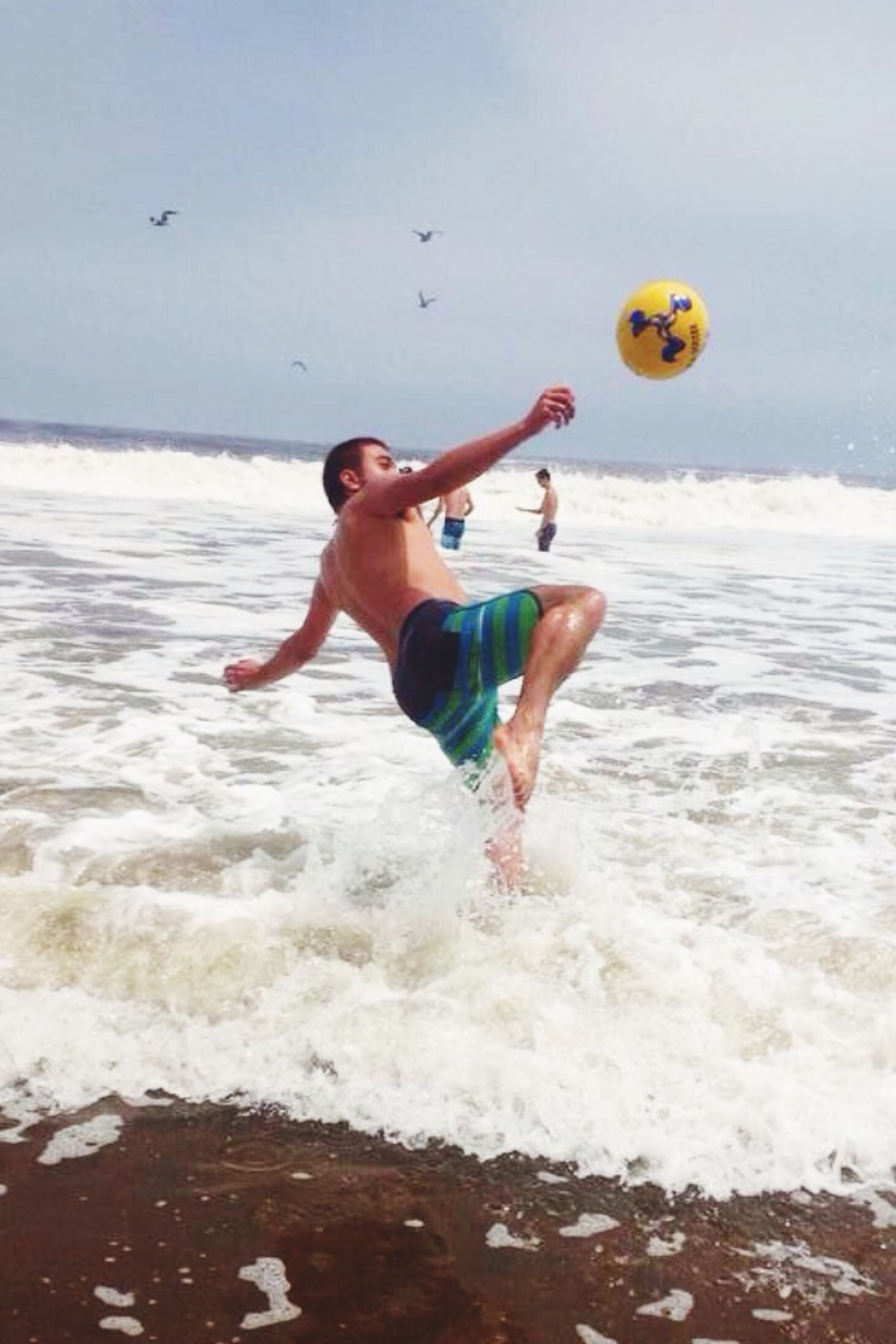 leisure activity, lifestyles, water, sea, full length, enjoyment, beach, fun, vacations, mid-air, jumping, shore, shirtless, childhood, motion, playing, wave, playful
