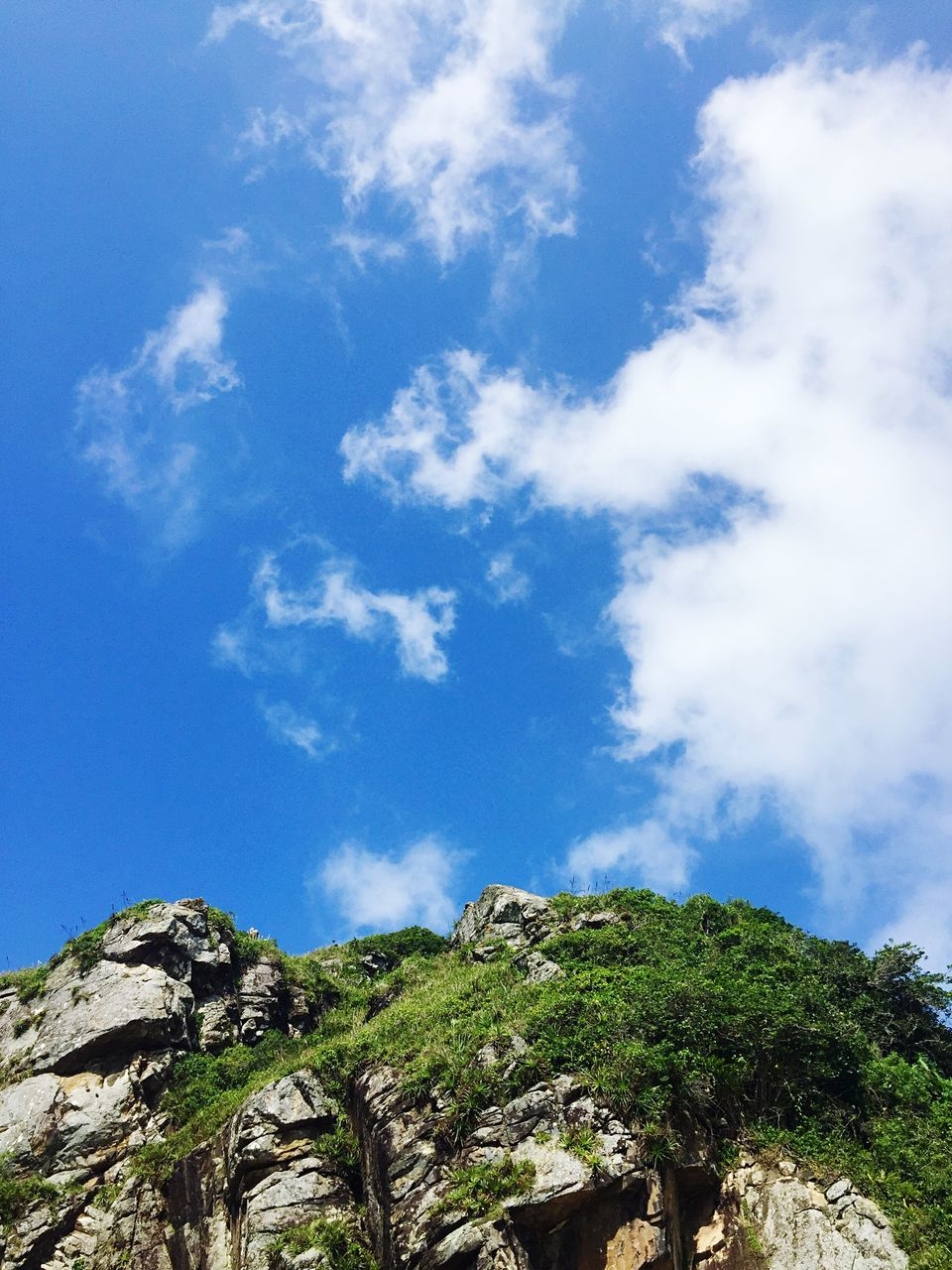 blue, beauty in nature, sky, nature, day, scenics, tranquility, cloud - sky, low angle view, tranquil scene, no people, outdoors, rock - object, mountain, tree
