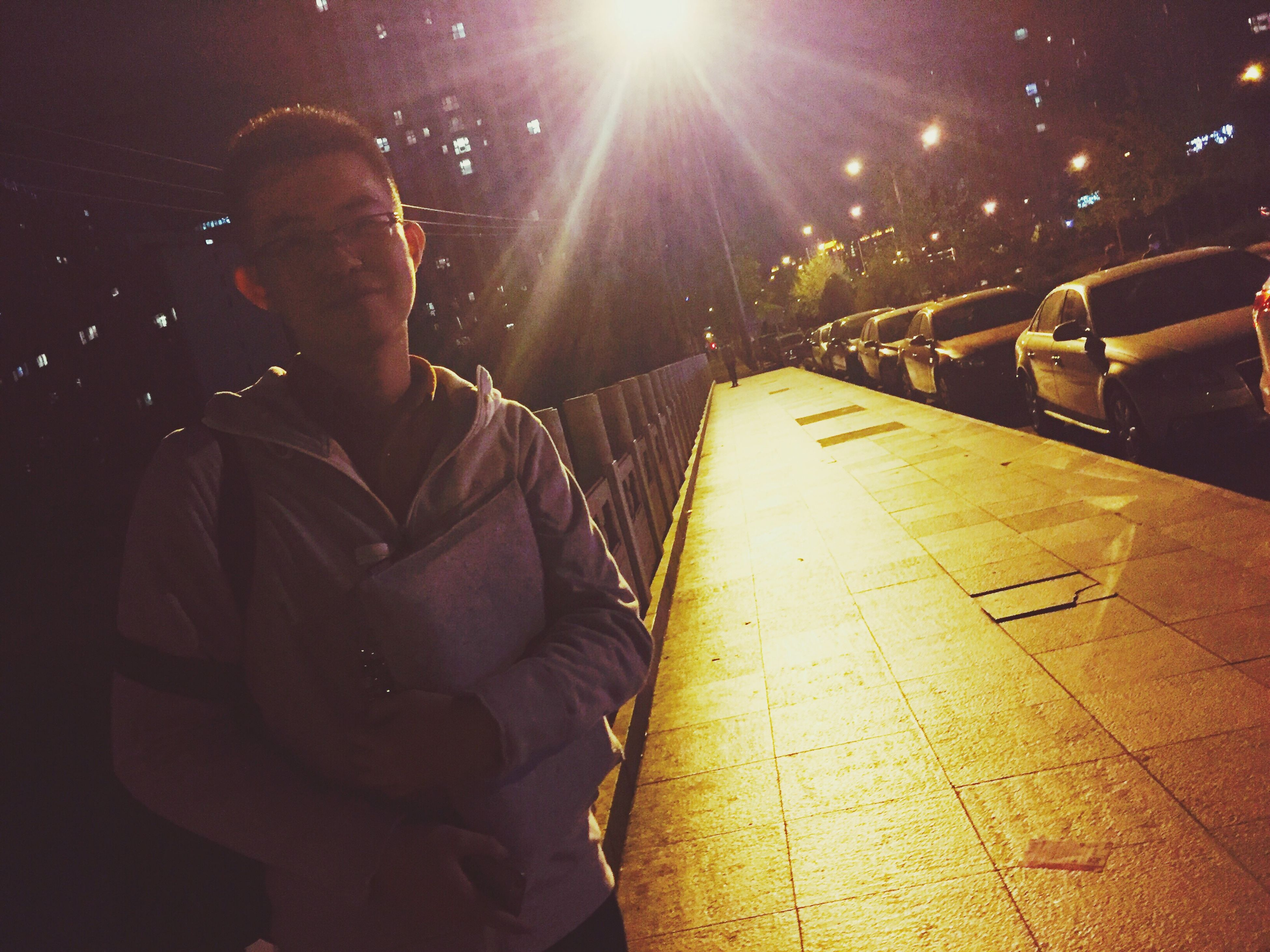 night, lifestyles, leisure activity, illuminated, men, casual clothing, togetherness, full length, sunlight, sitting, bonding, street, rear view, standing, person, outdoors