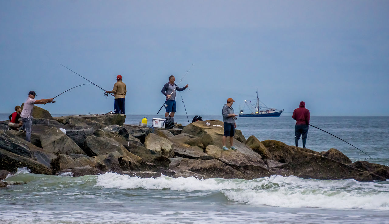 Men Fishing While Standing On Jetty Against Sky