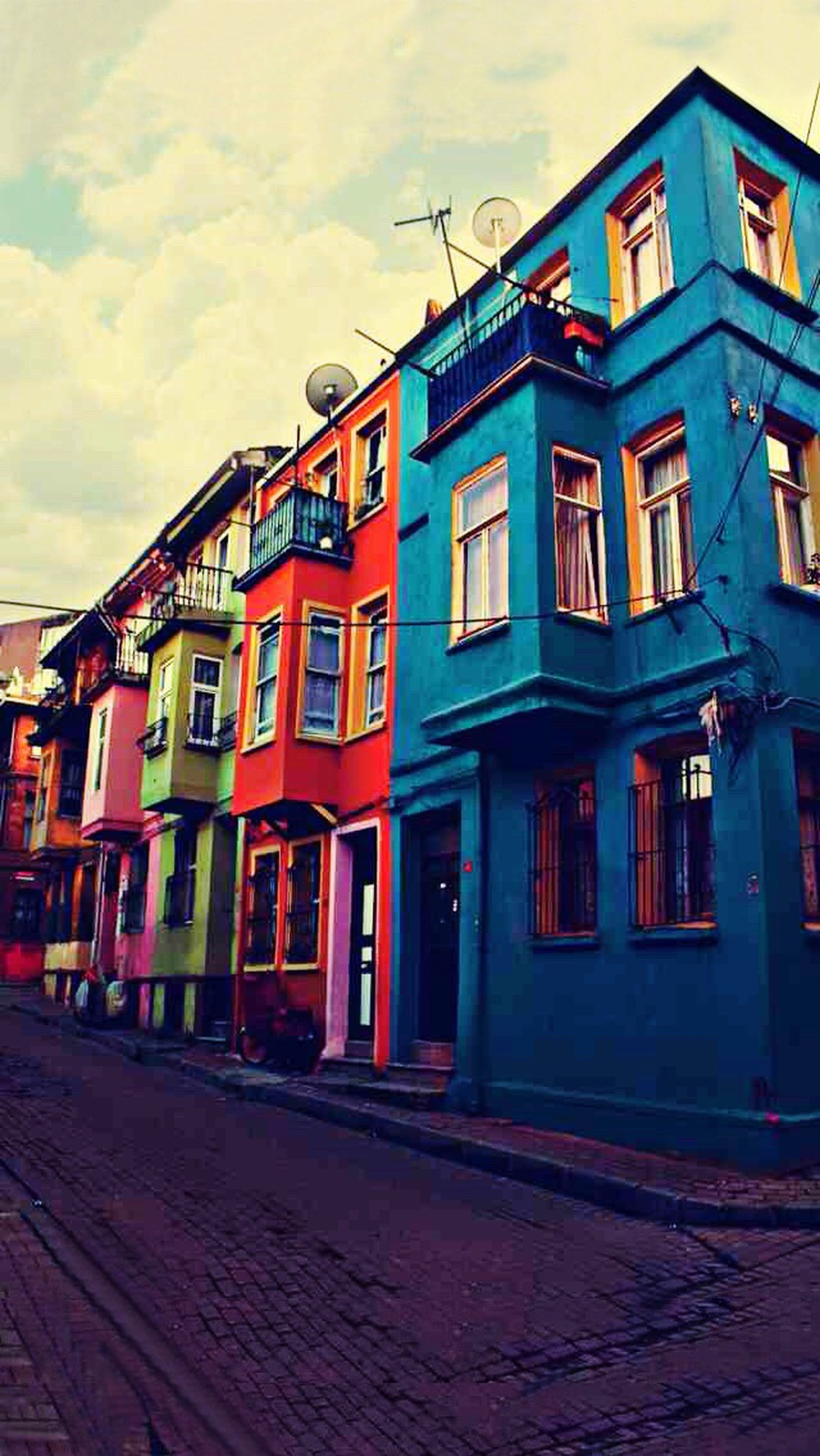 architecture, building exterior, built structure, multi colored, street, window, residential structure, sky, residential building, empty, colorful, city, cloud - sky, cloud, the way forward, day, outdoors, city life, no people, town, footpath, long, cloudy, residential district