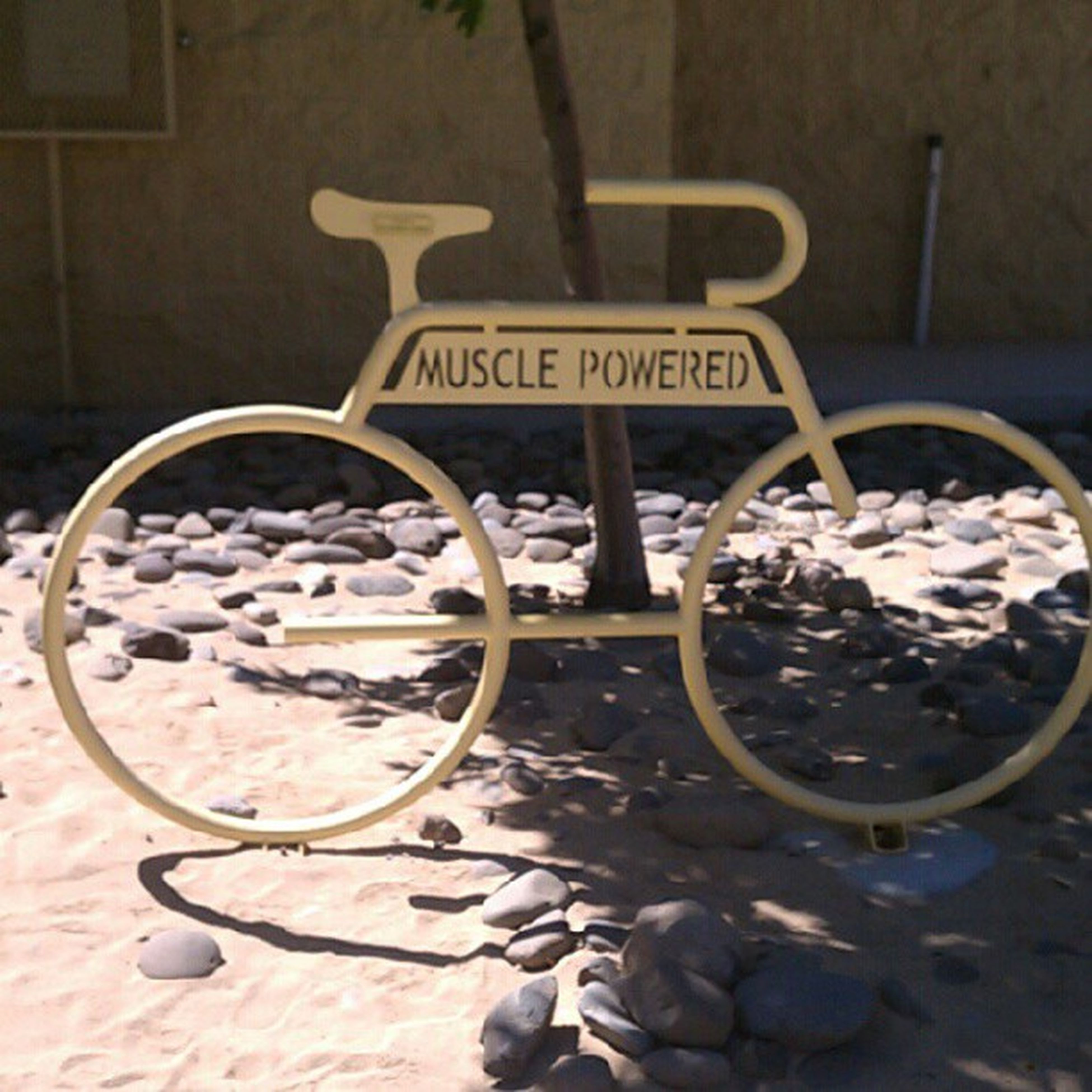 bicycle, transportation, text, mode of transport, no people, land vehicle, day, outdoors, stationary, street, high angle view, western script, close-up, communication, parking, parked, wheel, wall - building feature, sunlight, sidewalk