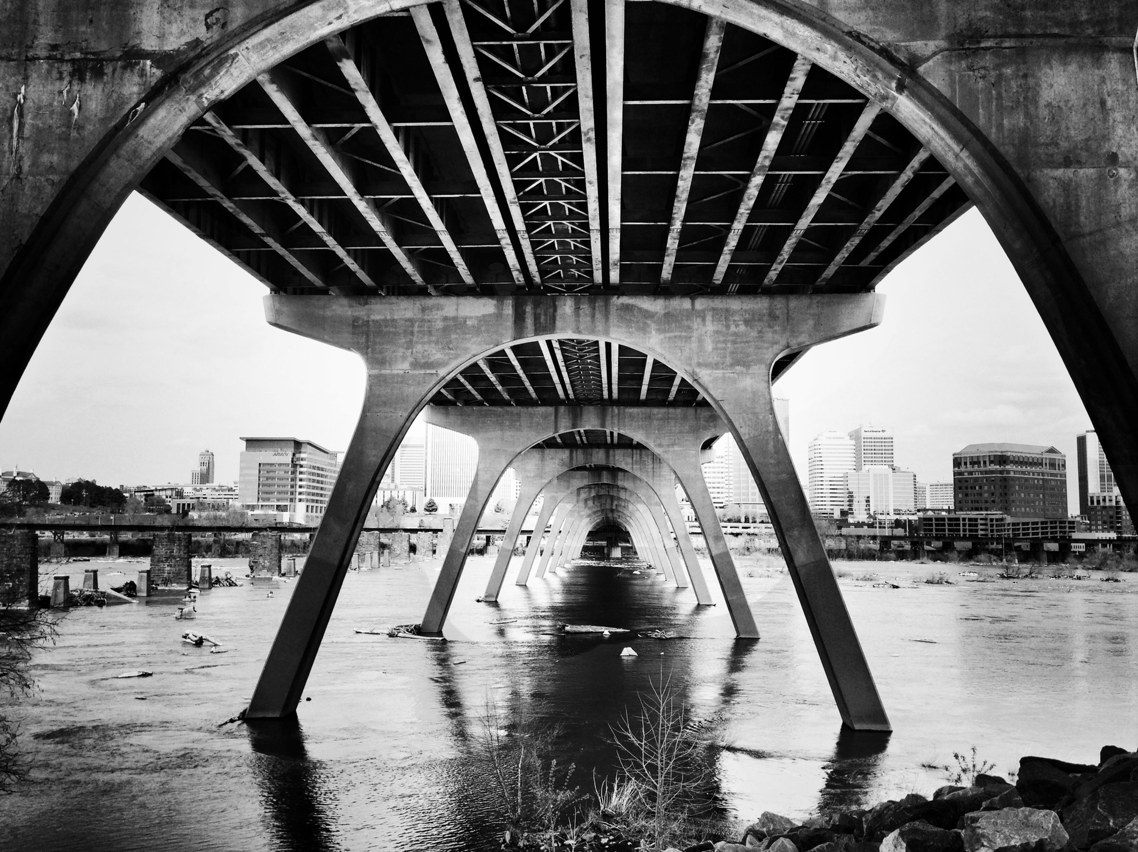 architecture, built structure, arch, bridge - man made structure, water, building exterior, connection, architectural column, city, river, sky, reflection, bridge, arch bridge, column, engineering, incidental people, travel destinations, day, city life