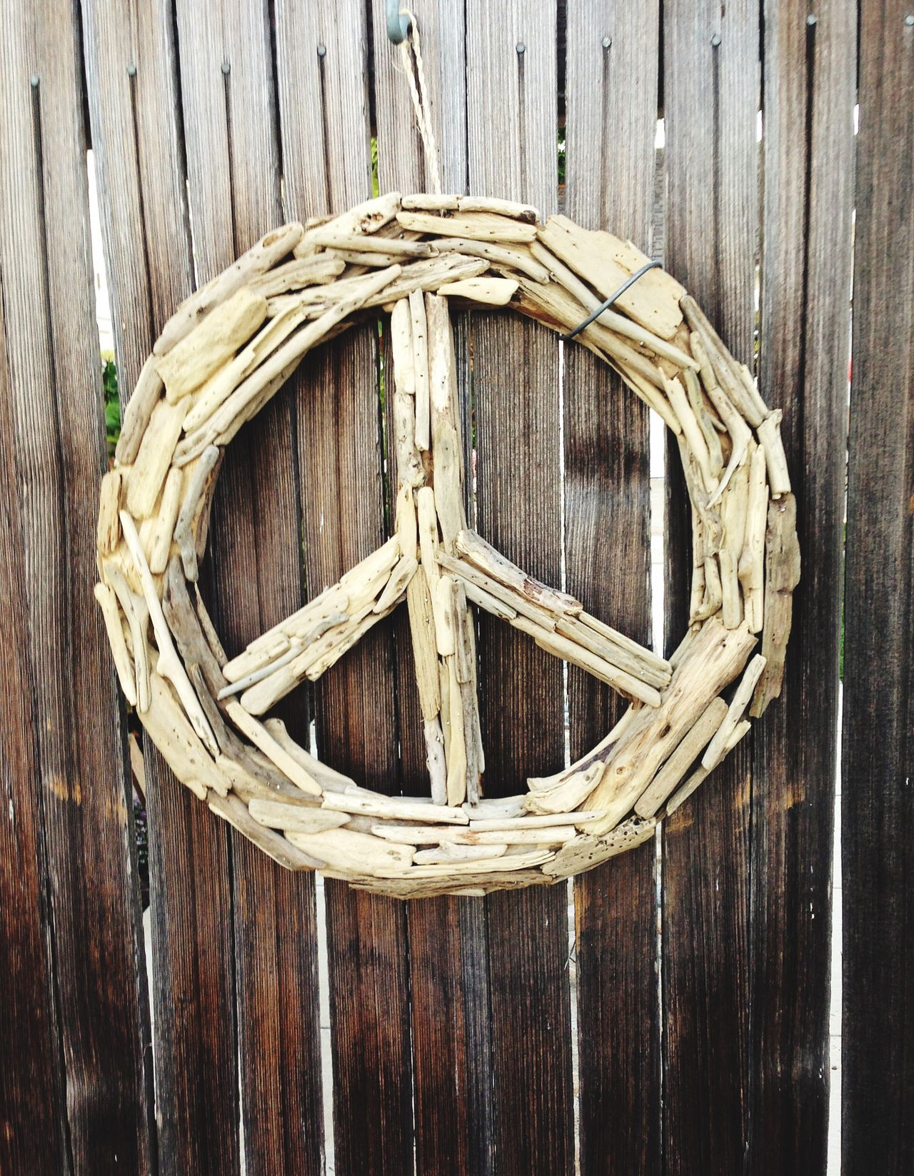 Deceptively Simple A peace sign hanging on a fence Peace Peace Peace Sign  Symbol Peace ✌ Hippie Seventies 70s Peace Signs Home Is Where The Art Is Symbols World Peace Handmade For You