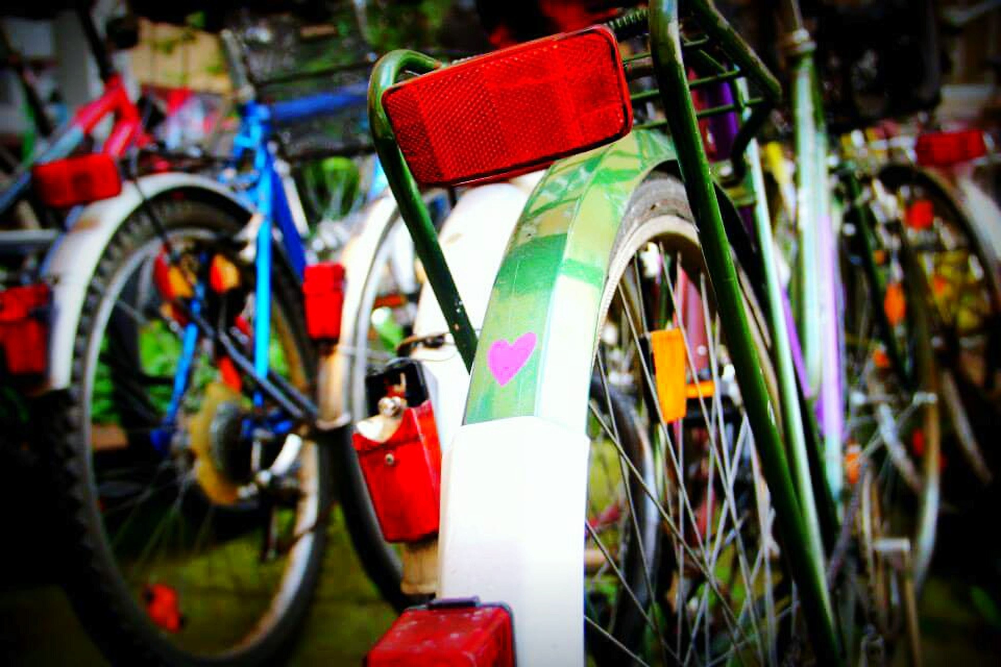 transportation, land vehicle, bicycle, mode of transport, focus on foreground, red, street, stationary, parking, car, selective focus, multi colored, close-up, parked, day, outdoors, road, no people, safety, motorcycle