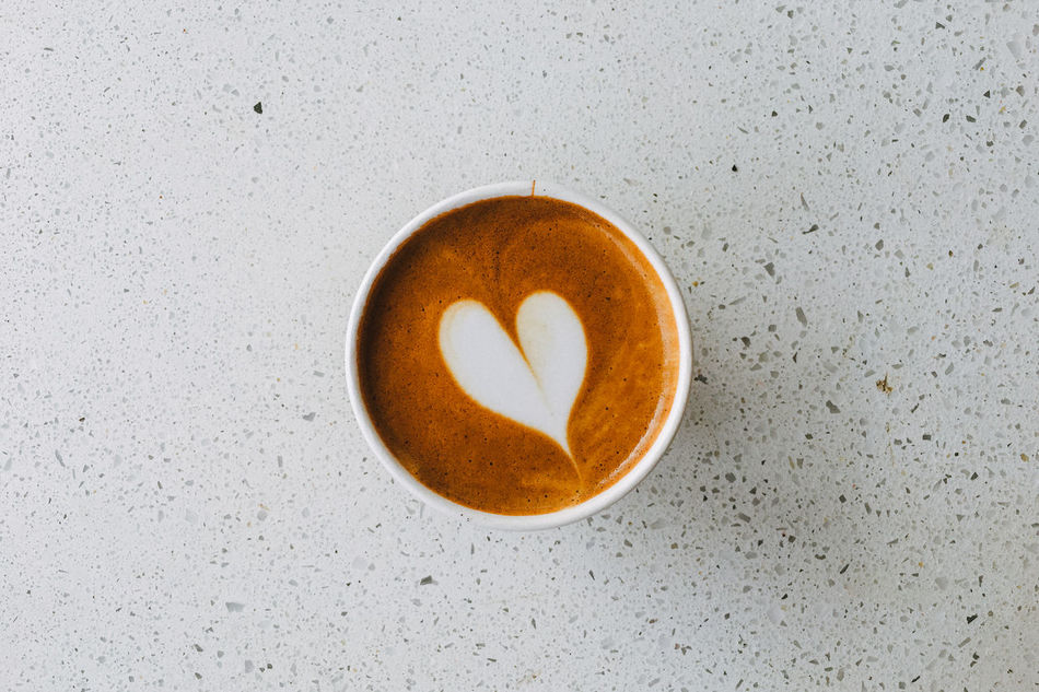 A freshly poured hot espresso drink on a counter top, the milk foam art poured in the shape of a heart. Bar Counter Cafe Close-up Coffee - Drink Coffee Break Coffee Shop Dairy Product Day Directly Above Espresso Espresso Macchiato Food And Drink Froth Art Frothy Drink Heart Shape High Angle View Indoors  Kitchen Counter Macchiato No People Non-alcoholic Beverage Paper Cup Table