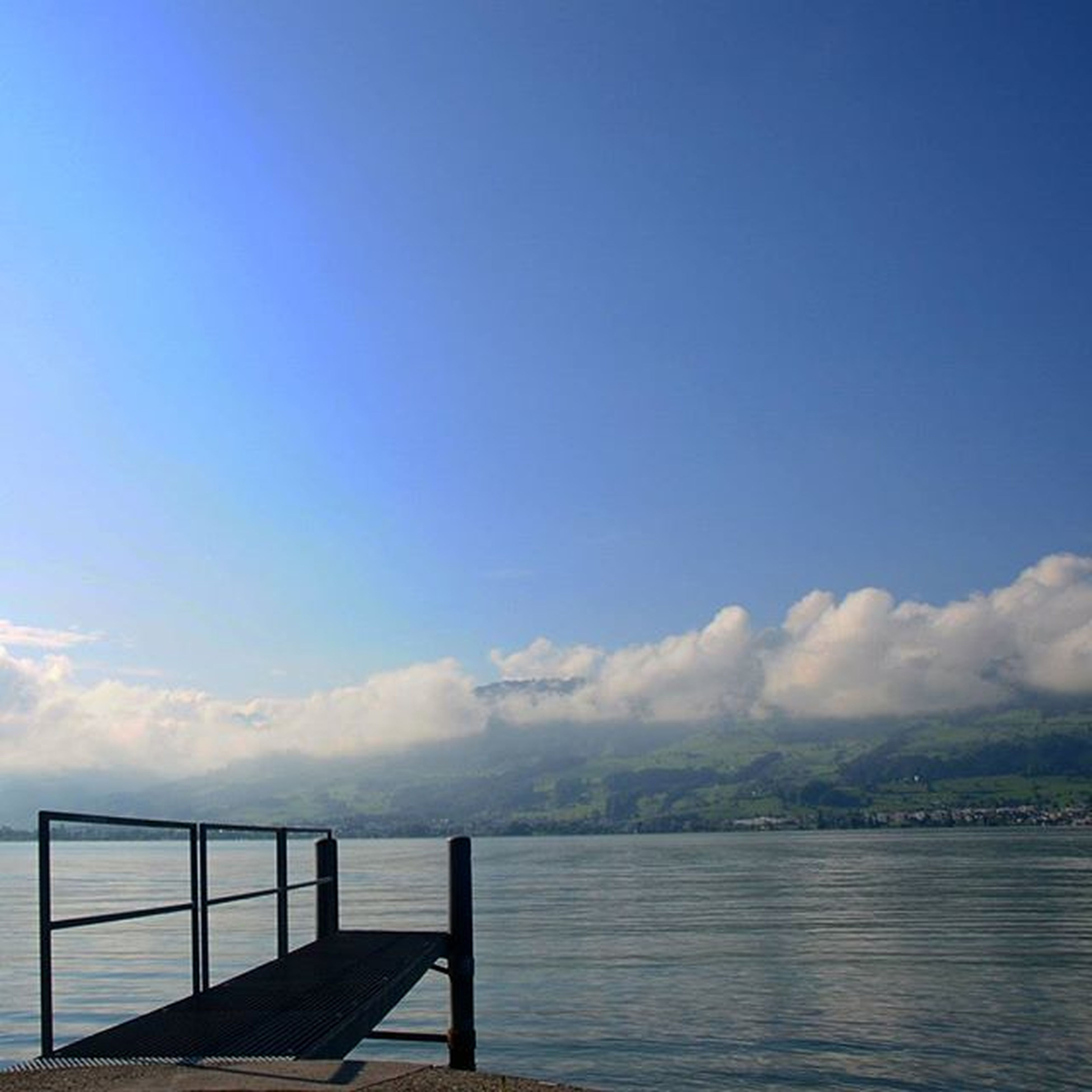 water, tranquil scene, sky, tranquility, scenics, sea, railing, beauty in nature, blue, nature, lake, pier, idyllic, cloud, cloud - sky, calm, waterfront, river, rippled, outdoors