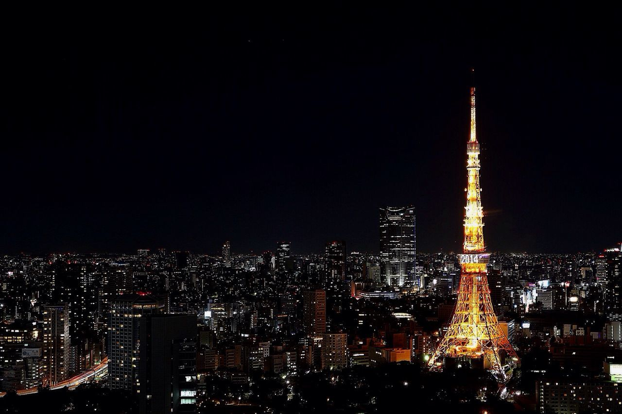 Illuminated Tokyo Tower In Cityscape Against Clear Sky At Night