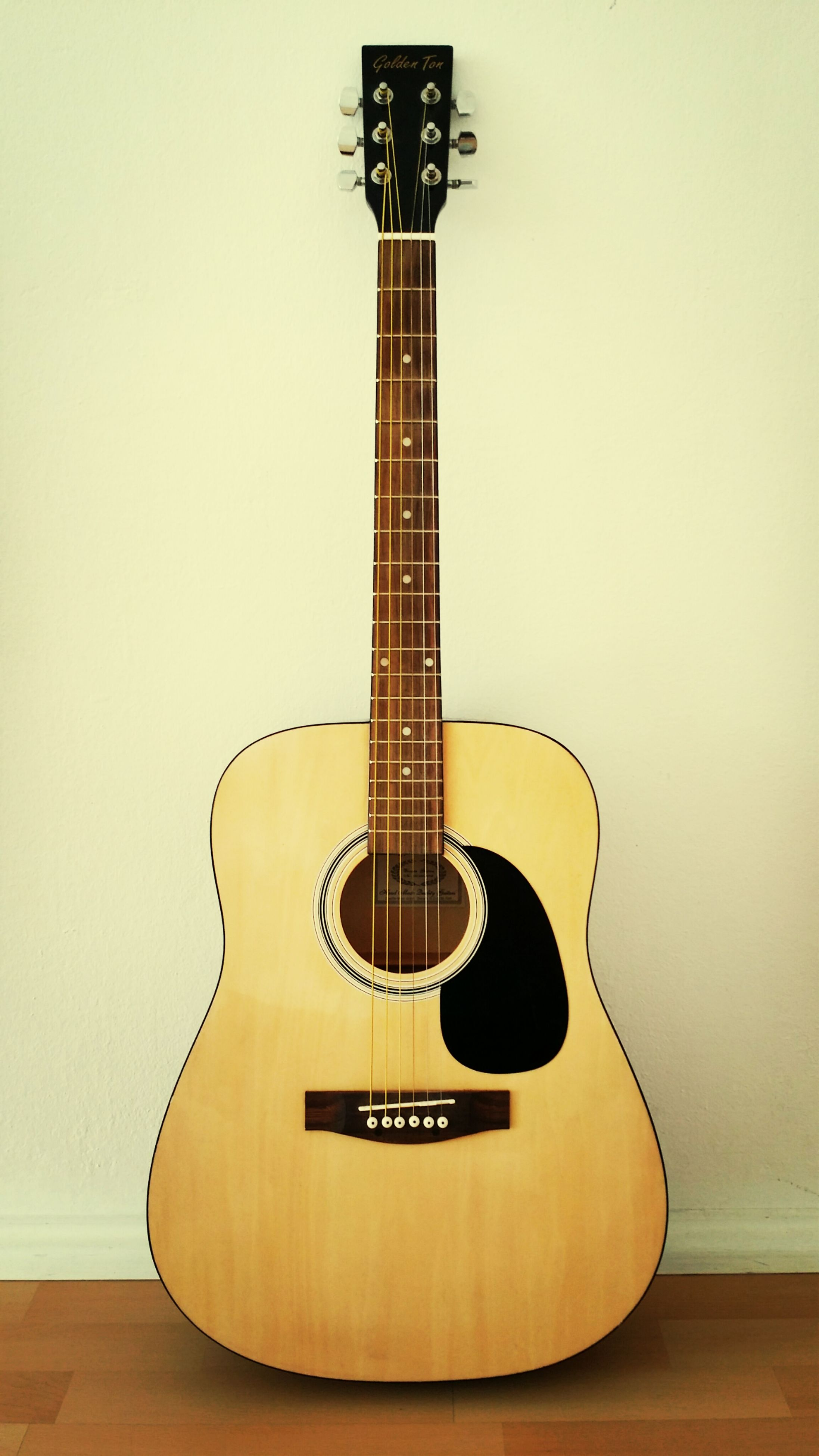 musical instrument, music, guitar, arts culture and entertainment, indoors, musical instrument string, musical equipment, communication, acoustic guitar, string instrument, still life, single object, close-up, illuminated, technology, wall - building feature, studio shot, low angle view, wood - material, no people