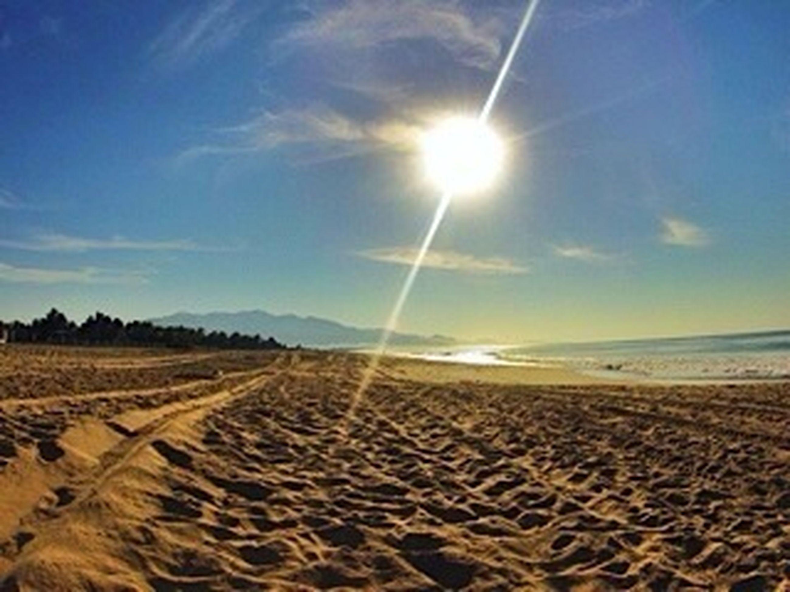 sand, beach, sun, sunlight, sky, tranquility, tranquil scene, sunbeam, scenics, nature, beauty in nature, landscape, shore, sunny, lens flare, sea, cloud, horizon over water, desert, cloud - sky