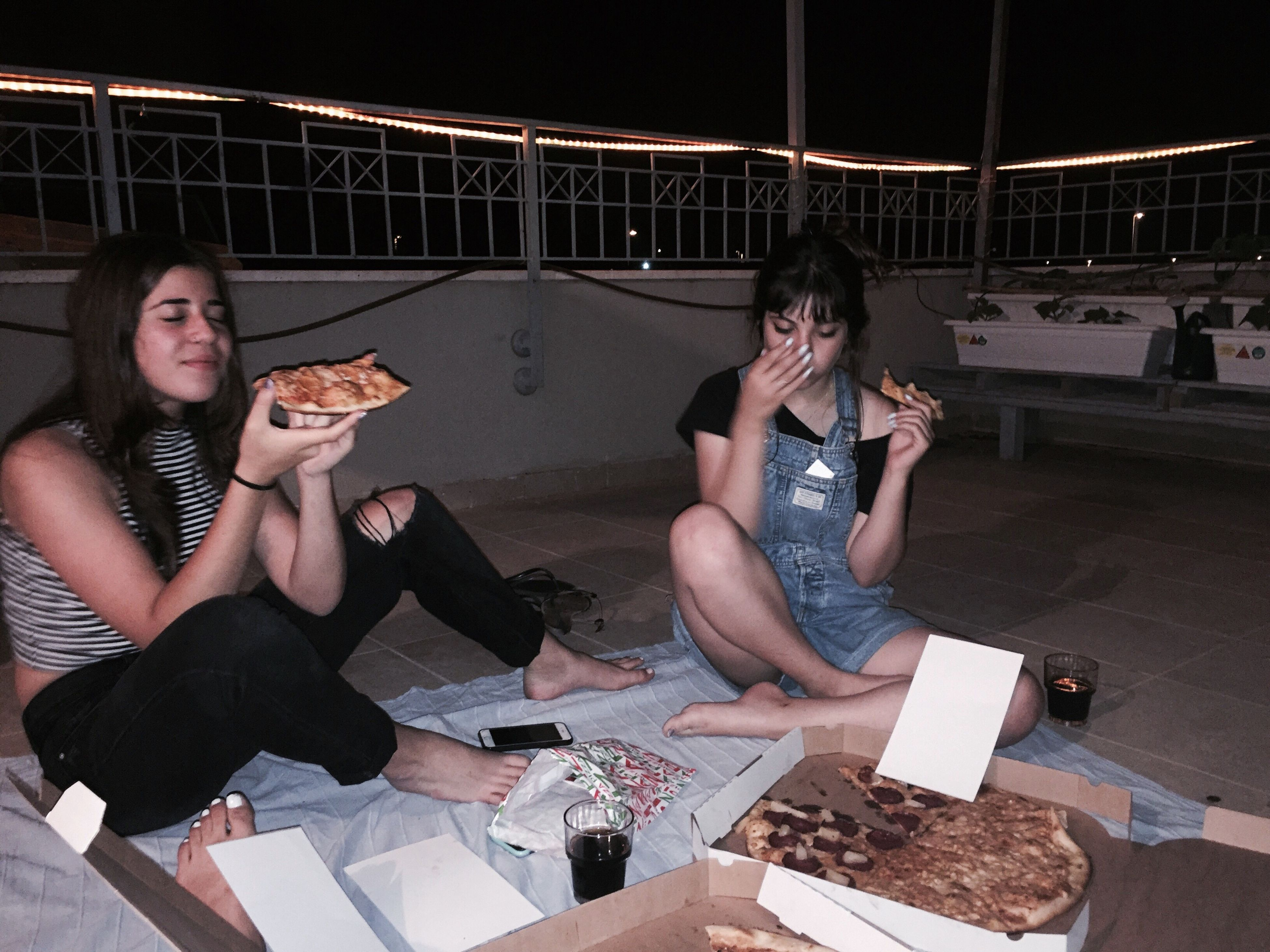 young adult, young women, sitting, food and drink, young men, night, two people, full length, holding, real people, leisure activity, togetherness, fun, indoors, food, playing, drink, pizza box, smiling, friendship