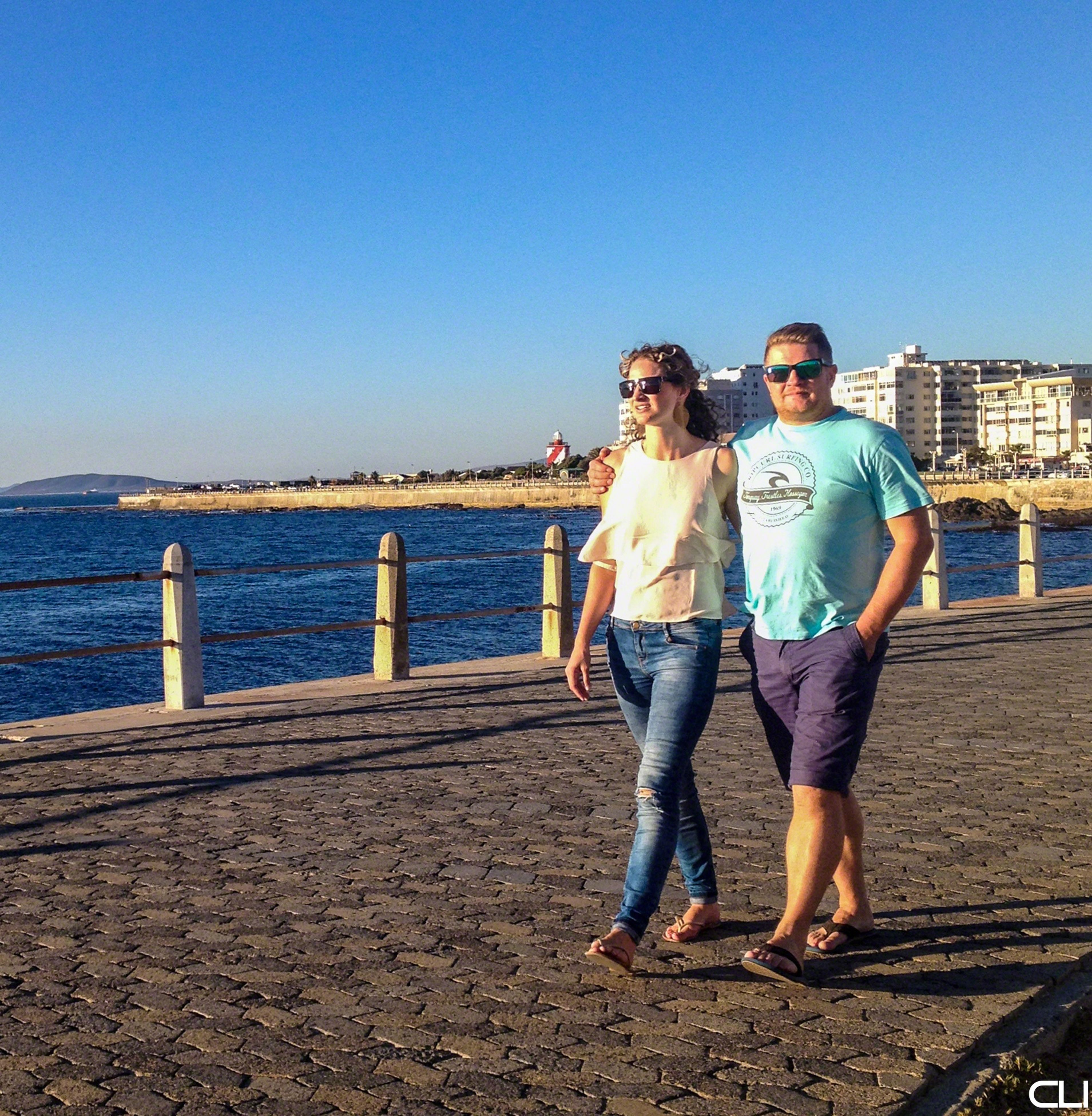 clear sky, lifestyles, full length, casual clothing, water, leisure activity, standing, copy space, blue, sea, togetherness, rear view, beach, boys, childhood, bonding, person