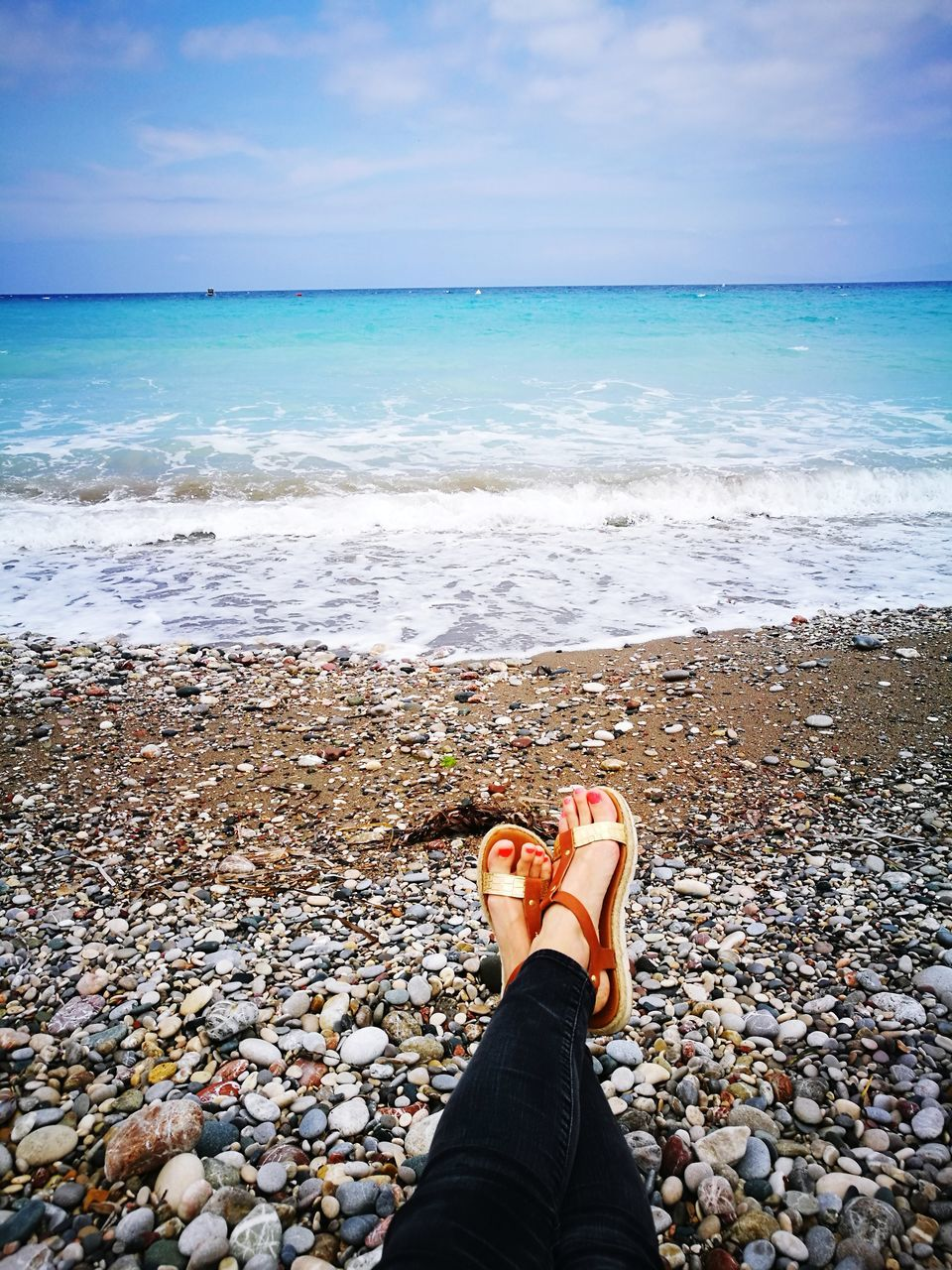 sea, beach, one person, horizon over water, water, human leg, low section, real people, shore, personal perspective, human body part, sky, day, nature, standing, women, beauty in nature, outdoors, pebble, lifestyles, scenics, wave, pebble beach, adult, people
