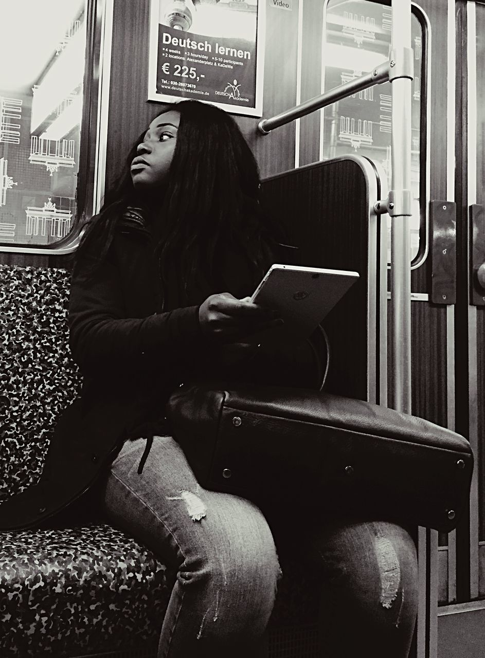 train - vehicle, sitting, public transportation, one person, real people, long hair, rail transportation, transportation, vehicle seat, young adult, young women, day, subway train, people