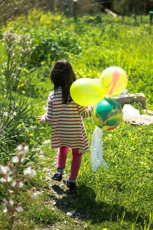 A little girl holding balloons and walking through green fields , in the countryside . Balloon Casual Clothing Childhood Children Only Countryside Uk Day Full Length Grass Green Color Growth Holding Balloons Little Girl Playing Nature Outdoors People Plant Real People Rear View Standing Striped T-shirt Tree Walking Yellow Balloons The Week On EyeEm