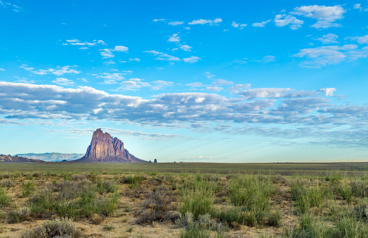"""Shiprock (Navajo: Tsé Bit'a'í, """"rock with wings"""" or """"winged rock"""" is a monadnock rising nearly 1,583 feet (482.5 m) above the high-desert plain of the Navajo Nation in San Juan County, New Mexico, United States. Its peak elevation is 7,177 feet. Beauty In Nature Cloud - Sky Day Desert Dramatic Sky Environment Geology Grass Green Color Landscape Mountain Natural Disaster Natural Phenomenon Nature New Mexico No People Outdoors Scenics Shiprock Sky Southwest  Southwestern Usa Tourism Travel Travel Destinations"""