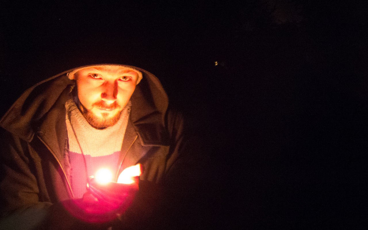 Portrait Of Man With Flame Wearing Hooded Jacket At Night