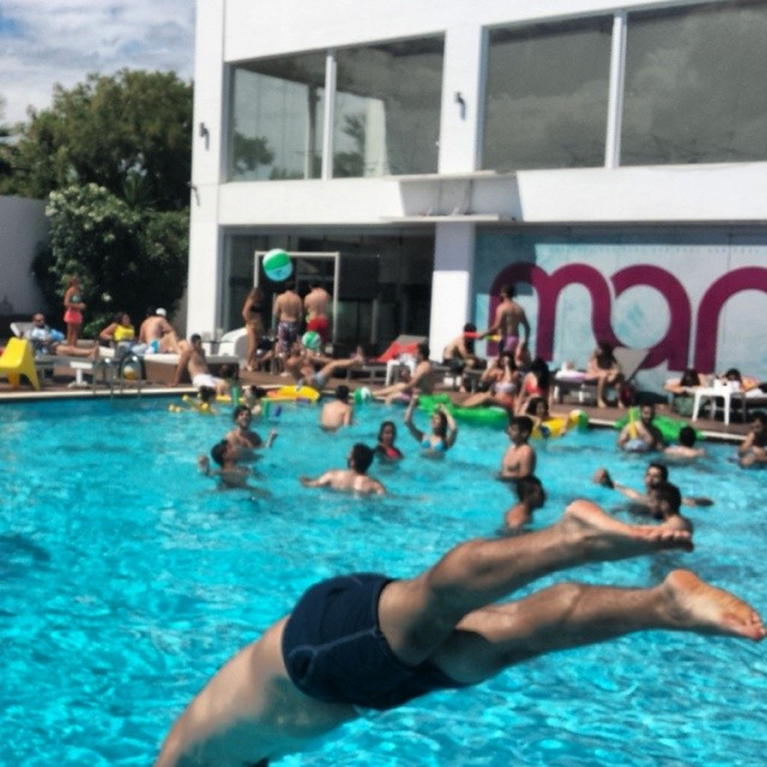 water, lifestyles, leisure activity, swimming pool, men, person, built structure, architecture, building exterior, large group of people, swimming, blue, turquoise colored, enjoyment, fun, waterfront, day
