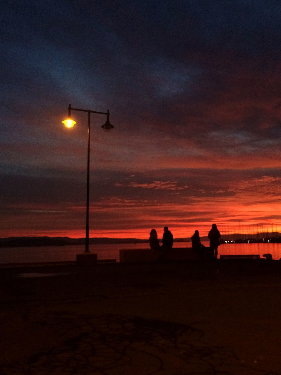 sunset, sky, silhouette, illuminated, nature, street light, cloud - sky, outdoors, beauty in nature, scenics, sitting, lifestyles, real people, night, sea, leisure activity, beach, togetherness, men, water, people