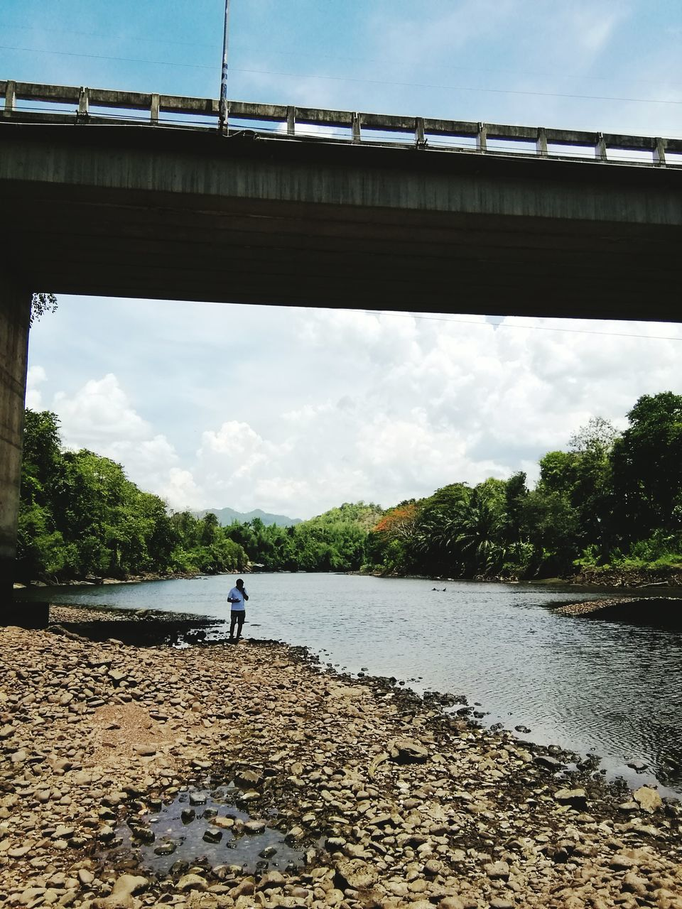 bridge - man made structure, connection, sky, river, cloud - sky, real people, day, architecture, water, rear view, one person, full length, built structure, outdoors, standing, nature, transportation, leisure activity, men, tree, lifestyles, under, people