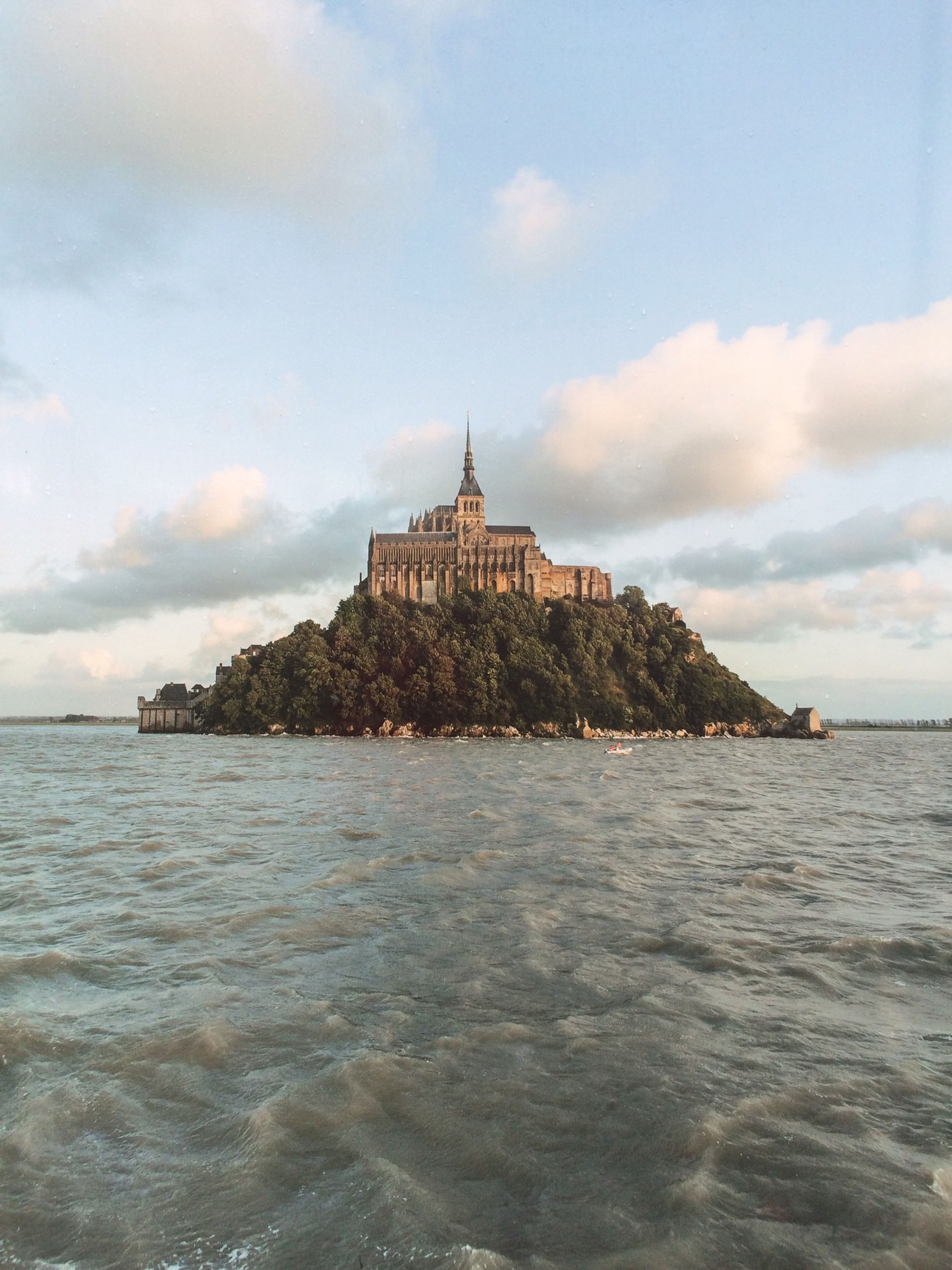 architecture, built structure, water, building exterior, sea, sky, waterfront, cloud - sky, famous place, travel destinations, religion, tourism, travel, history, spirituality, horizon over water, place of worship, cloud, tower, cloudy