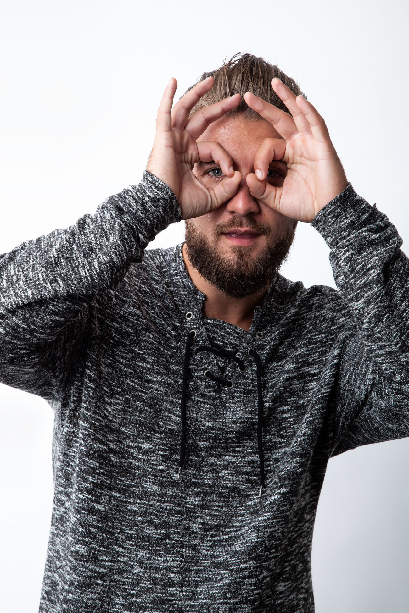 Handsome young man smiling, making binoculars with his hands isolated on white background Adult Arms Beard Binocular Casual Close-up Curly Eye Farsightedness Focus Gesture Hand Isolated Looking Male Myopia One People Person Portrait Standing Studio Surprised View Young