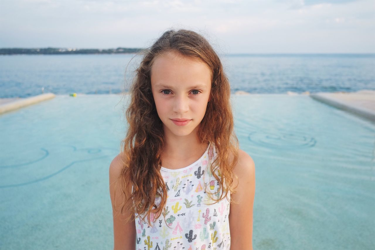 Girl looking straight into a camera. Sea Water Childhood Horizon Over Water Girls Real People Beach One Person Front View Looking At Camera Leisure Activity Outdoors Elementary Age Nature Focus On Foreground Standing Scenics Beauty In Nature Day Vacations Portrait Authentic Moments