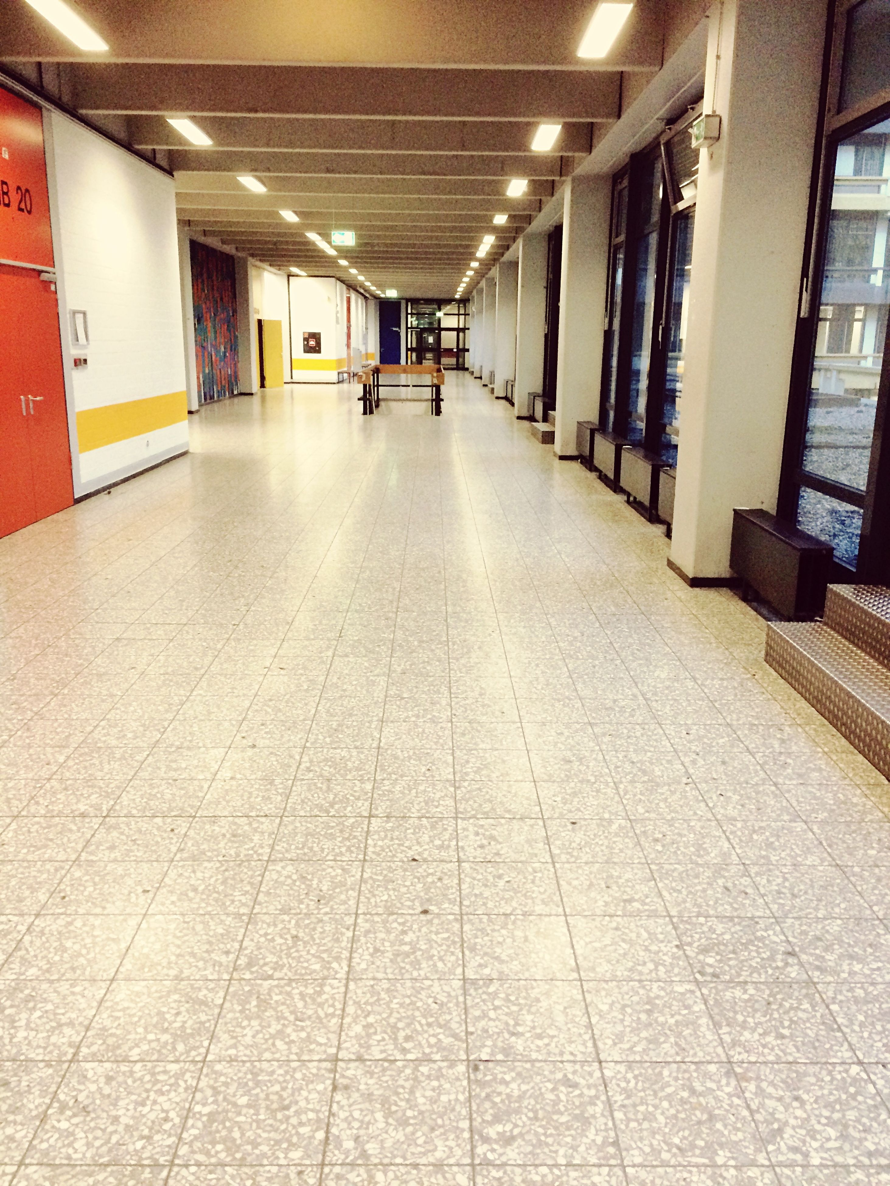 indoors, illuminated, architecture, the way forward, corridor, built structure, empty, tiled floor, diminishing perspective, flooring, ceiling, lighting equipment, in a row, absence, vanishing point, long, narrow, incidental people, building, underpass