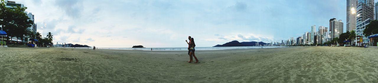 Man And Woman Walking On Shore At Beach
