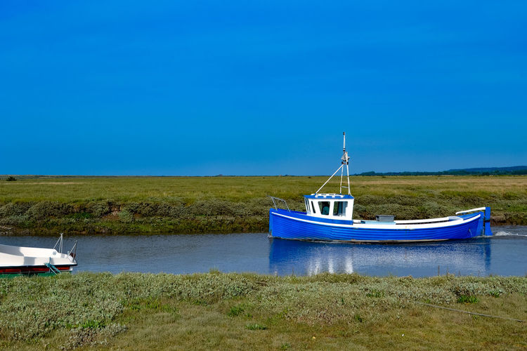Blue fishing boat on river, Tollesbury. Blue Boat Clear Sky Day Estuary Grass Landscape Mode Of Transport Moored Nature Nautical Vessel No People Outdoors River Channel Sea Sky Transportation Travel Destinations Water