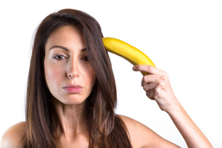 Conceptual portrait of a young woman trying to shoot herself with a banana gun. Space for text. Adult Banana Diet Fun Funny Gun HEAD Isolated Joke Background Beauty Concept Conceptual Contraception Crazy Creative Dangerous Discomfort Face Food Fruit Girl Grotesque Hand Healthy