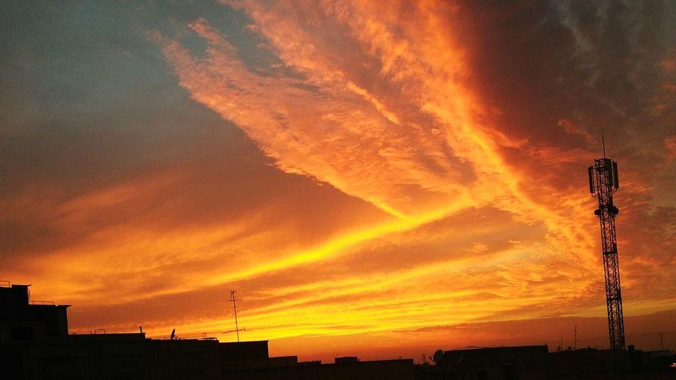 Hometown sunrise... Sunset Orange Color Sky Cloud - Sky Beauty In Nature Dramatic Sky Outdoors Nature Sunset Silhouette Orange Color Sky Built Structure Architecture Scenics Building Exterior Cloud - Sky Majestic Beauty In Nature Cloud Atmosphere High Section Outline Dramatic Sky Outdoors First Eyeem Photo