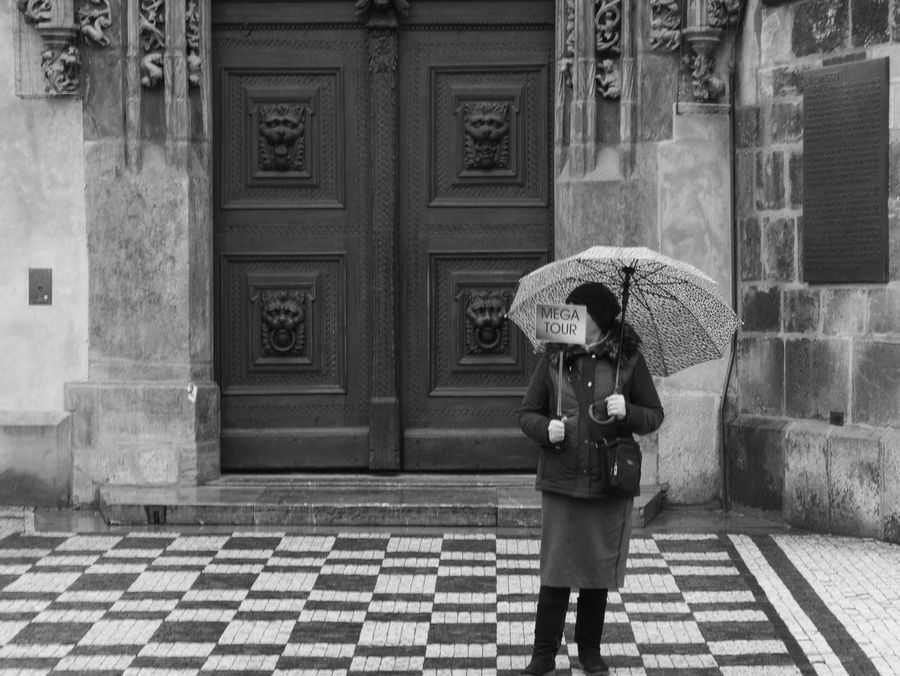 Reversed reality. This woman/ travel guide was somehow lost. Standing in the mid center of this big town, she was searching for her group. I always thought it should be the opposite. WomeninBusiness Woman Portrait Lost Travel Guide Umbrella People In The Background Real People Walking Prague Popular Photos Showcase: February The Week On Eyem Travel EyeEm Best Shots City Life EyeEm Gallery People Photography Black And White Built Structure Rainy Days Capture The Moment Street Photography Textured