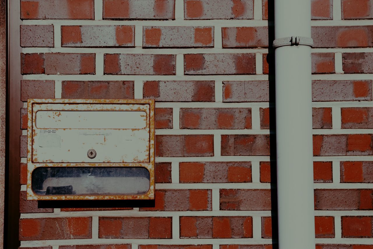 Pipe With Mail Box On Brick Wall