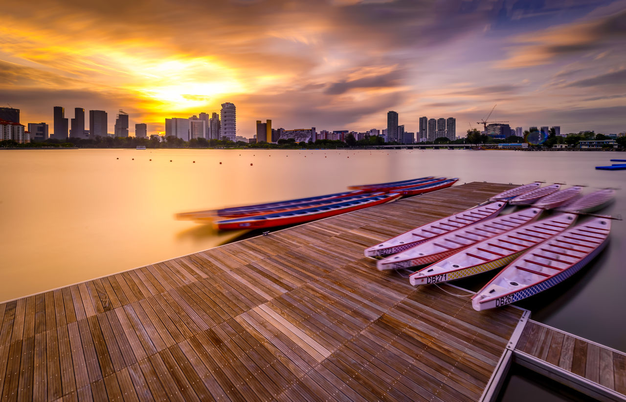 architecture, built structure, building exterior, skyscraper, city, sunset, sky, cityscape, urban skyline, cloud - sky, no people, travel destinations, outdoors, water, nature, day