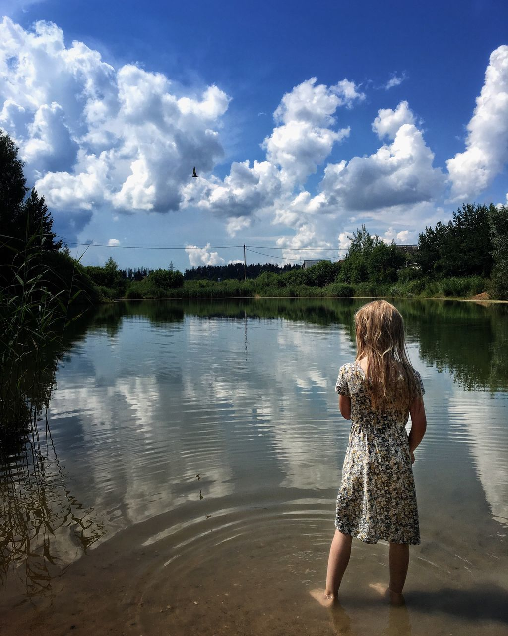 water, one person, real people, sky, standing, day, rear view, nature, tree, leisure activity, casual clothing, outdoors, childhood, cloud - sky, full length, tranquility, beauty in nature, young adult, young women, people