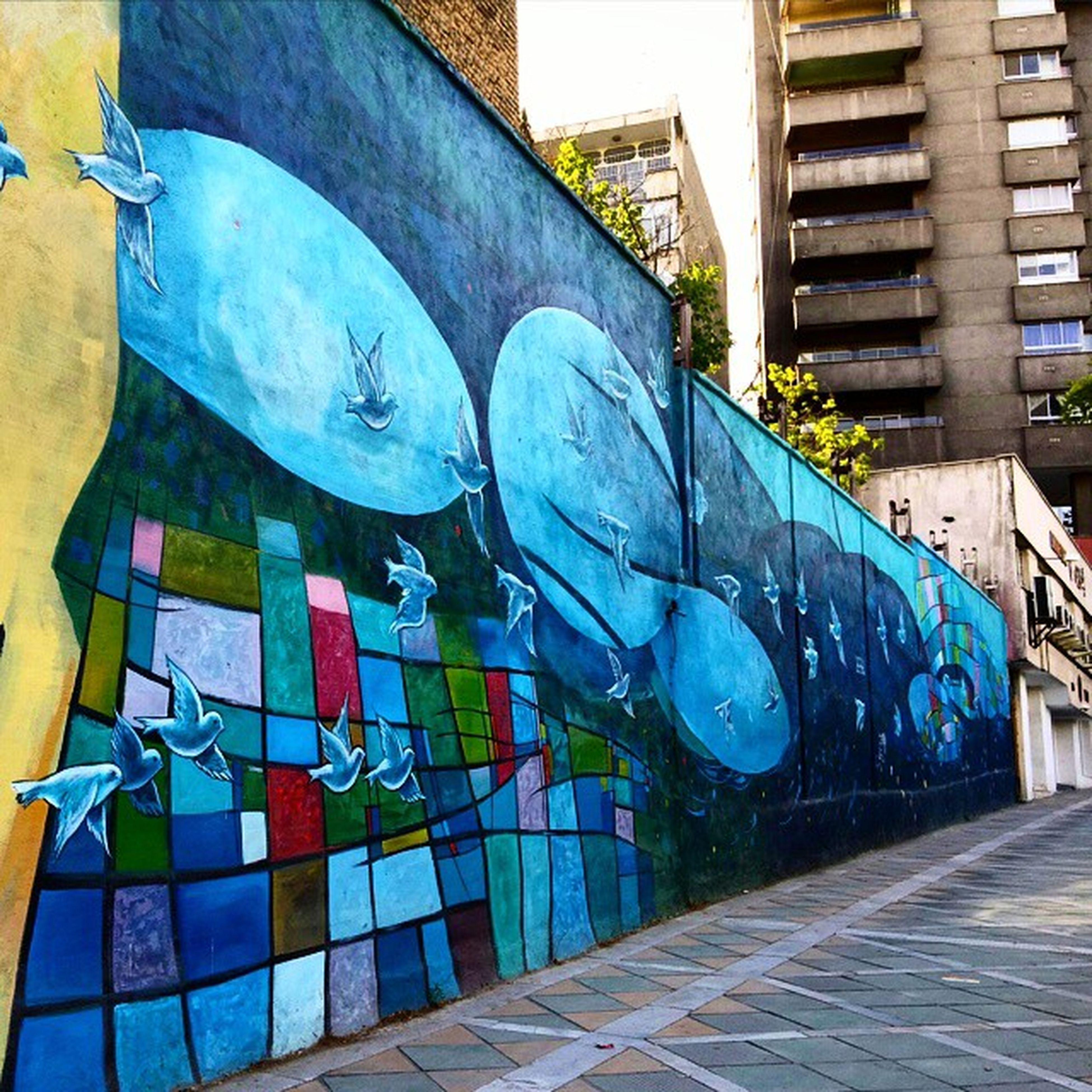 graffiti, art, built structure, art and craft, architecture, creativity, building exterior, multi colored, wall - building feature, blue, day, no people, street, outdoors, sidewalk, wall, empty, sunlight, street art, in a row